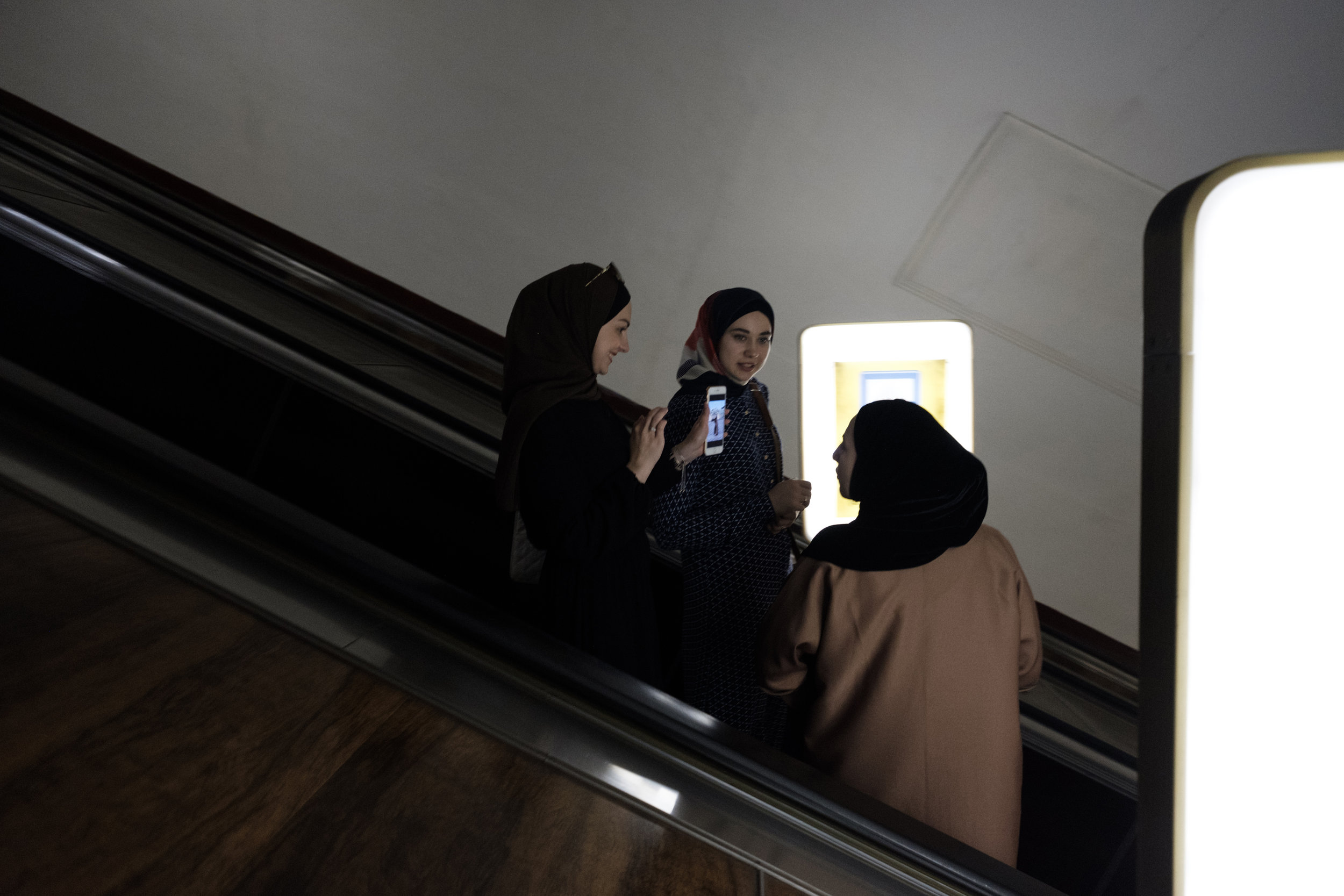Three young women rides the escalator at Arsenalna Metro in Kiev Ukraine