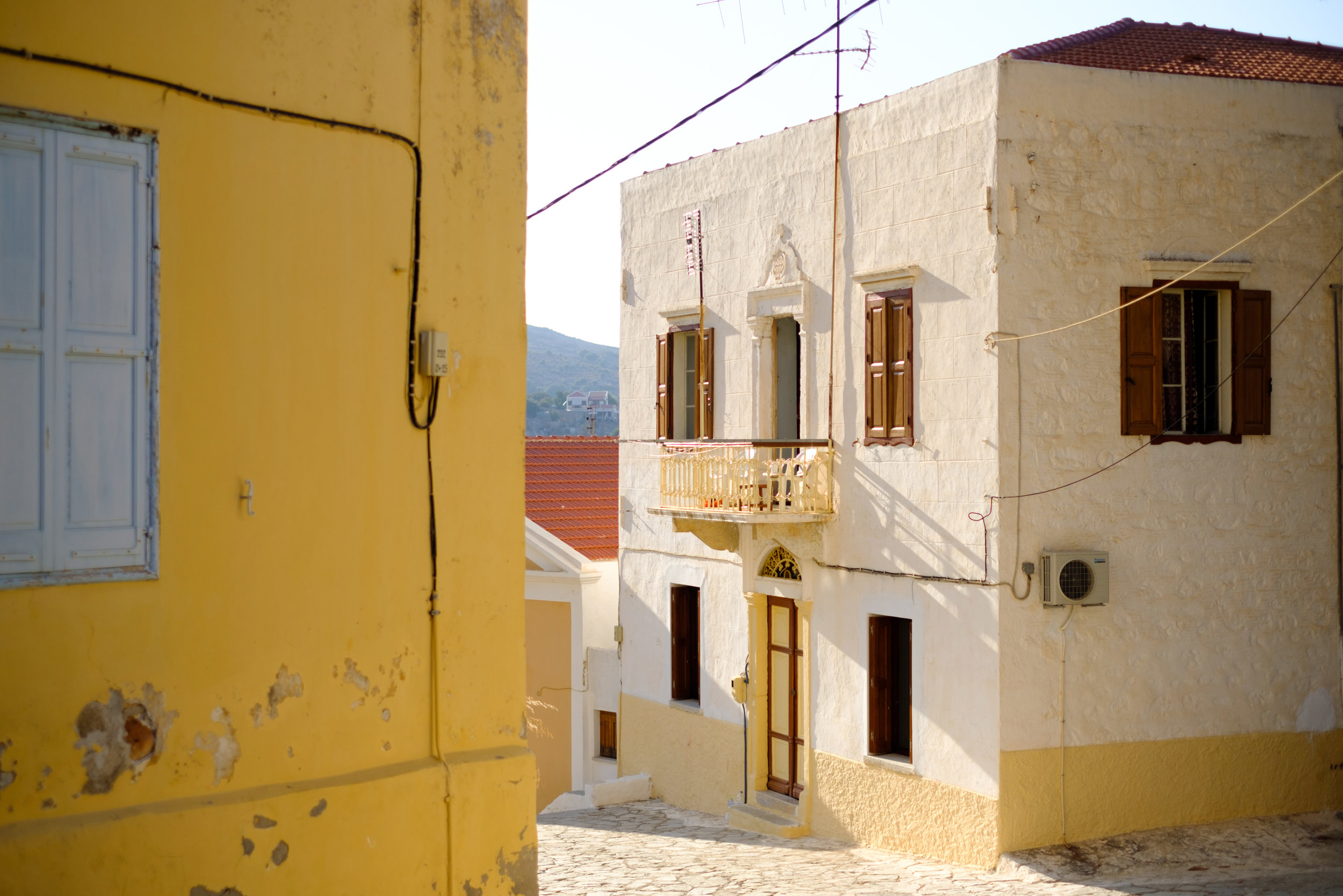 A yellow house with a balcony on the island of Symi in Greece
