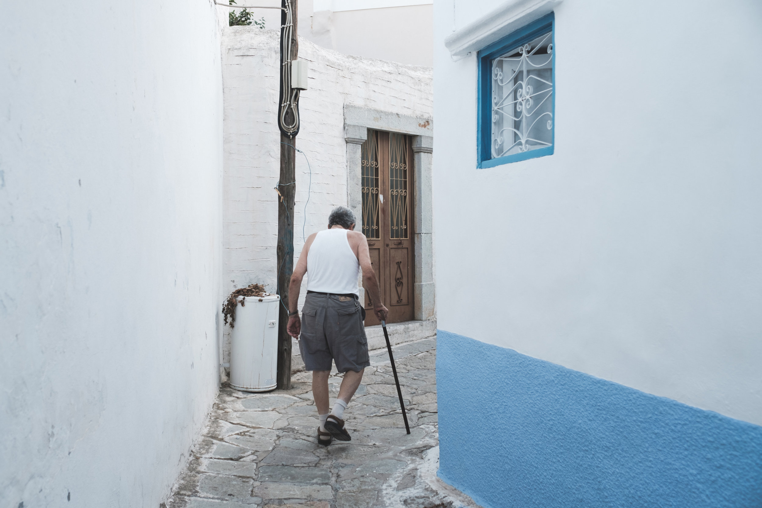 An elderly man walks with a cane through the back alleys of Symi in Greece