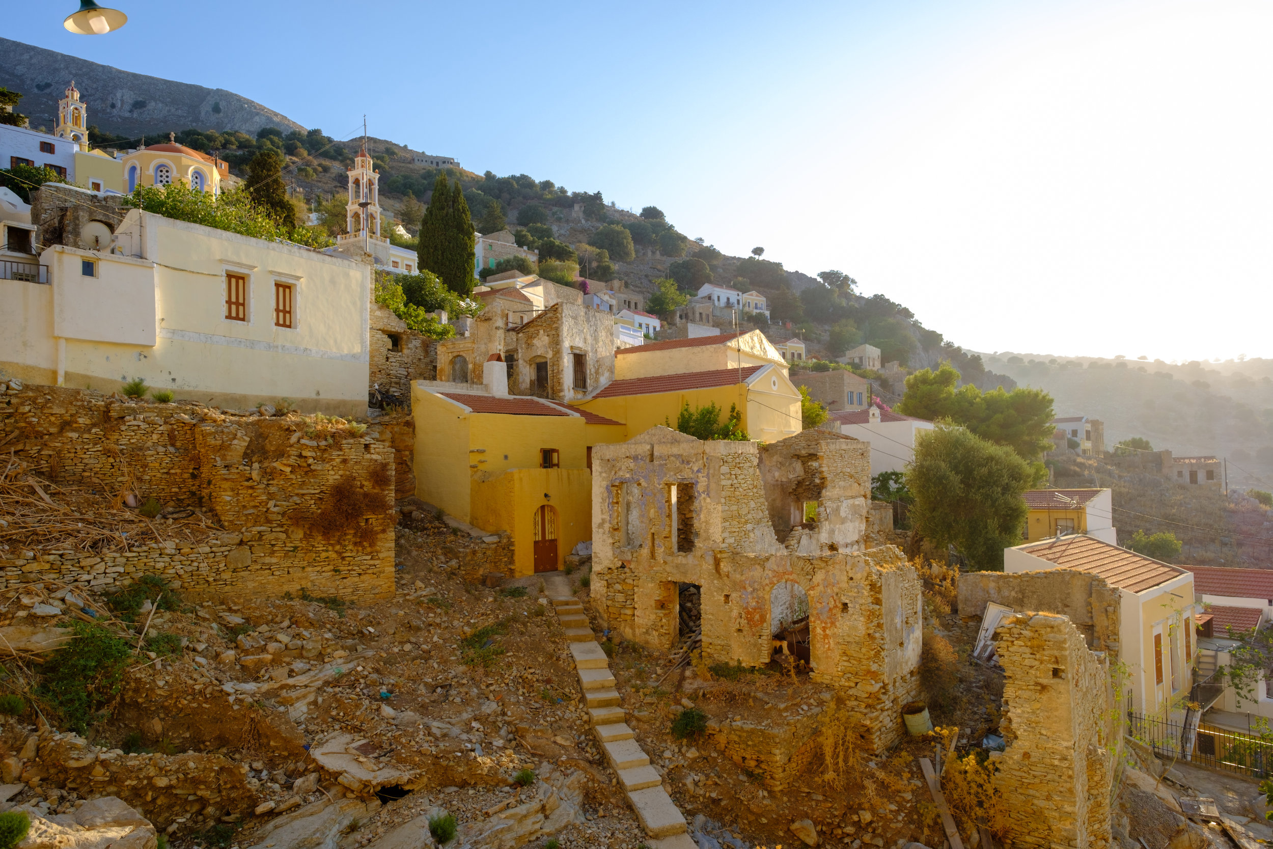 The steep hillside on the island of symi in Greece. Pastel coloured houses