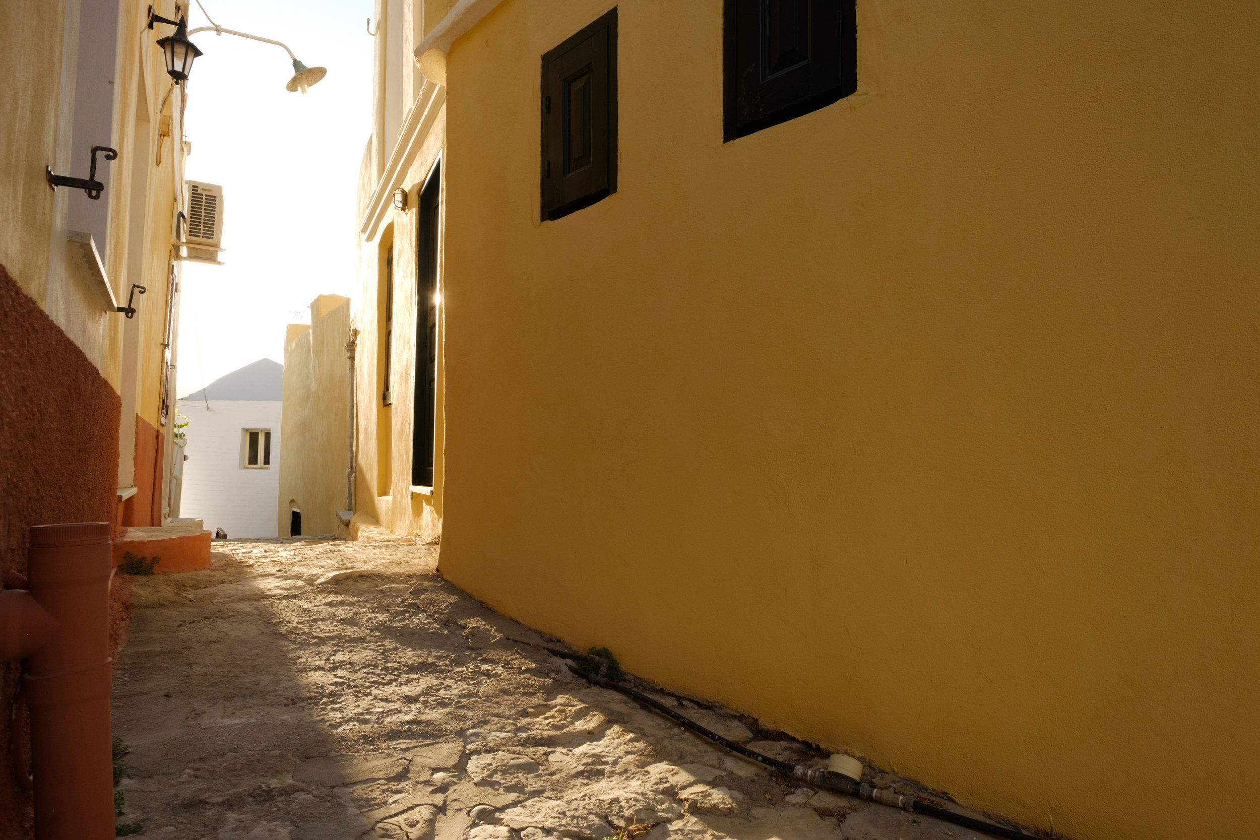 late afternoon sun in a back alley on the island of symi in greece