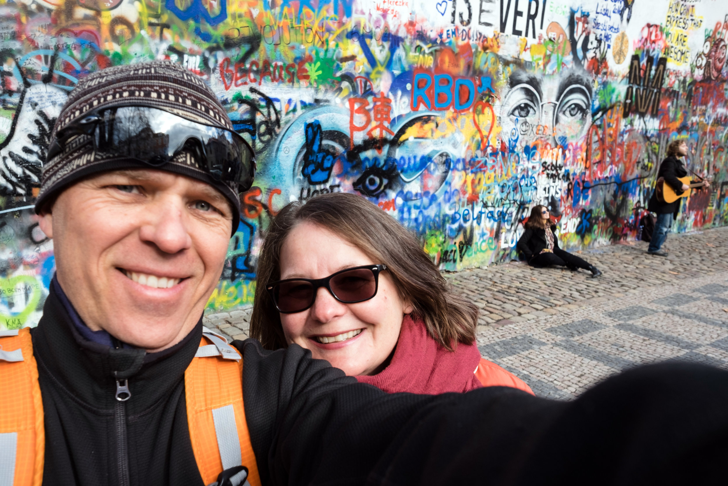 A couple taking a selfie at the John Lennon Wall in Prague