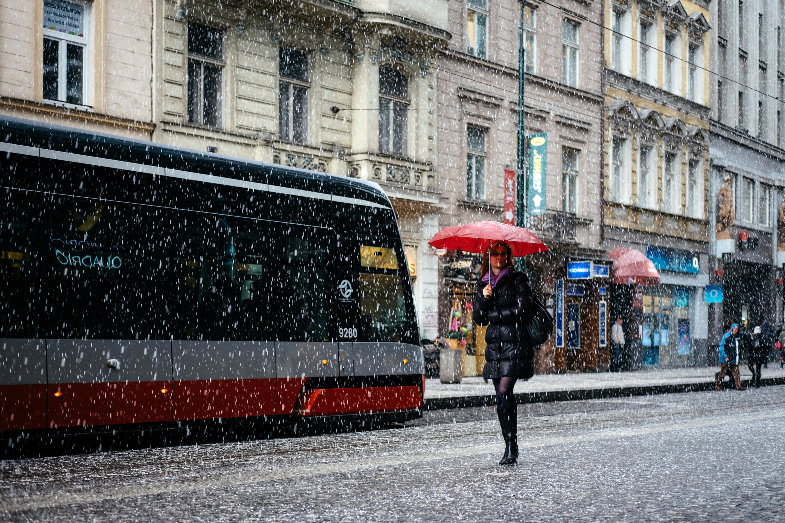 Prague Tram and a woman crossing the street with an umbrella