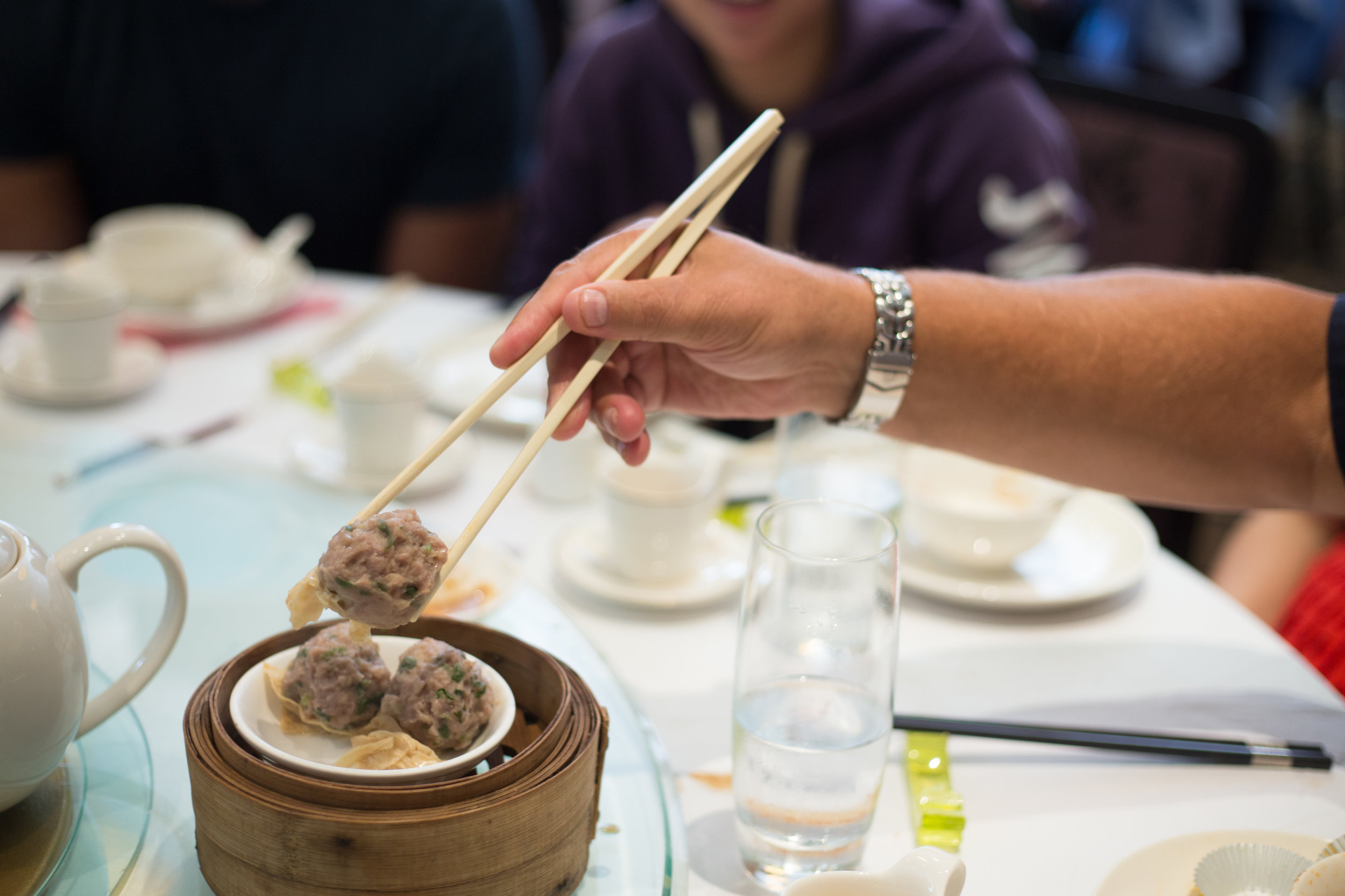 A man hold chop stick at a dim sum lunch in hong kong