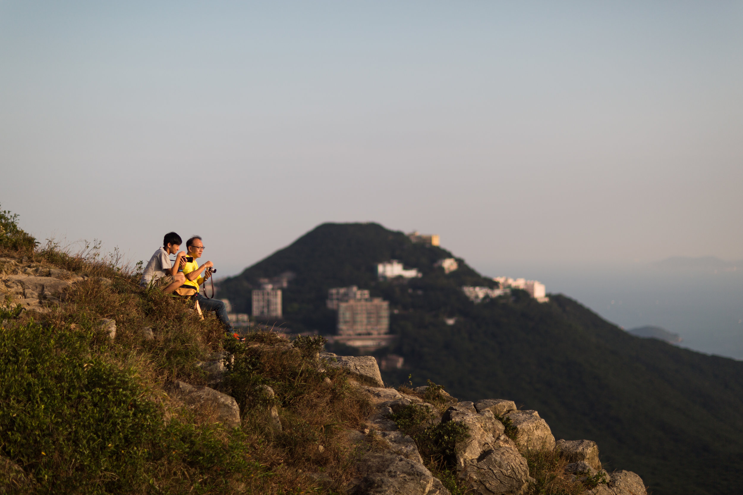 A father and son photographing the evening at High West in Hong Kong