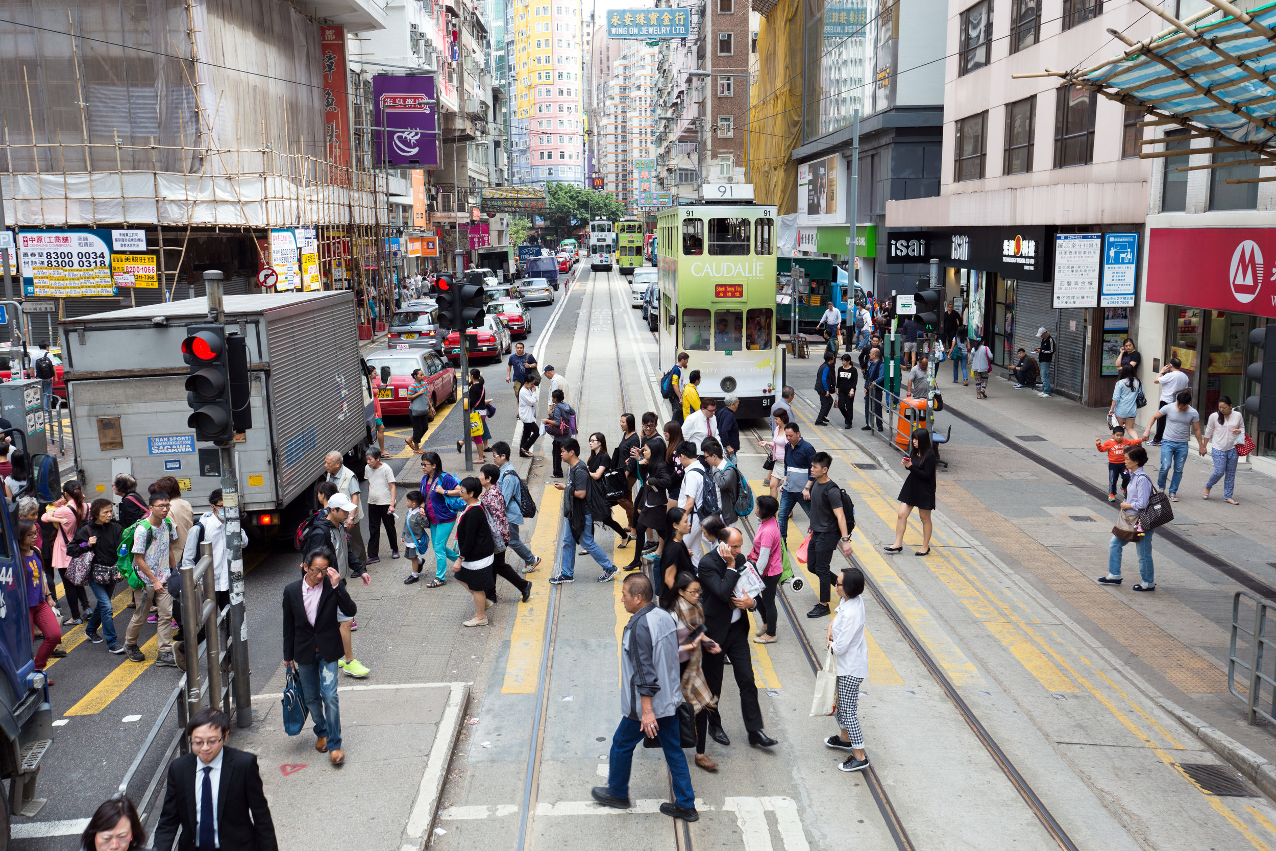 A busy street in Wan Chai Hong Kong with pedestrians and trams