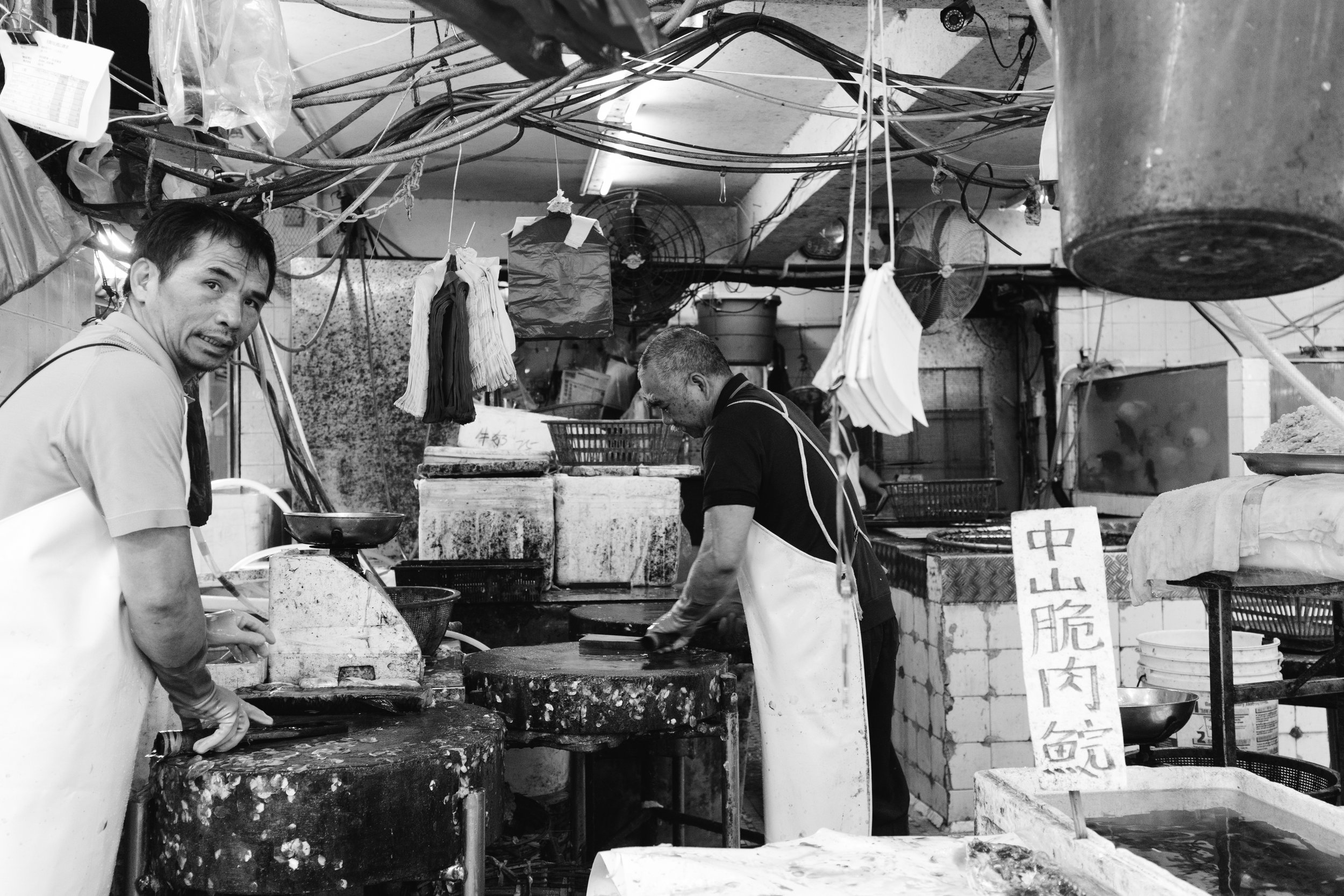 Two men are working at a fish market in Wan Chai Hong Kong