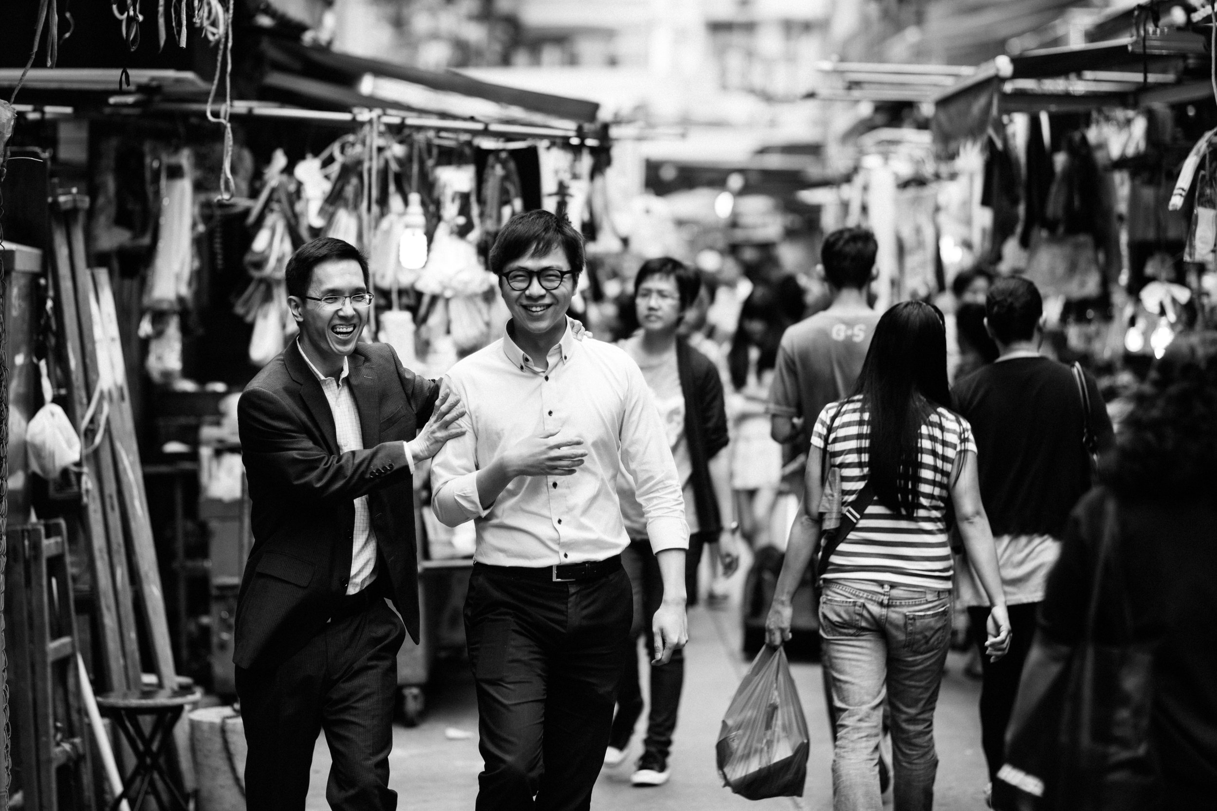 Two male friends a laughing walking through a food market in Wan Chai Hong Kong