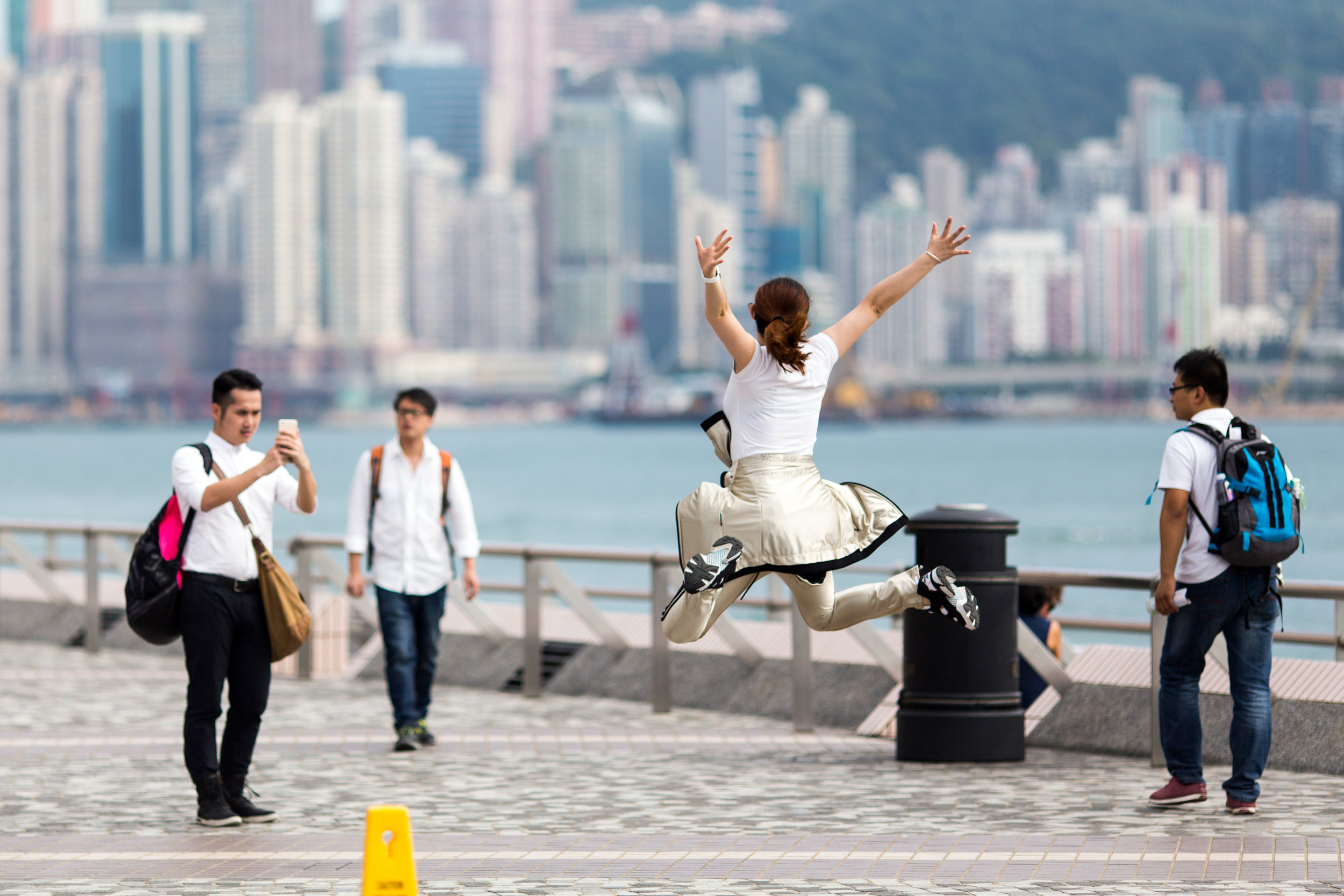 A bride is posing for wedding photos along the promenade at the Kowloon Public Pier in Hong Kong