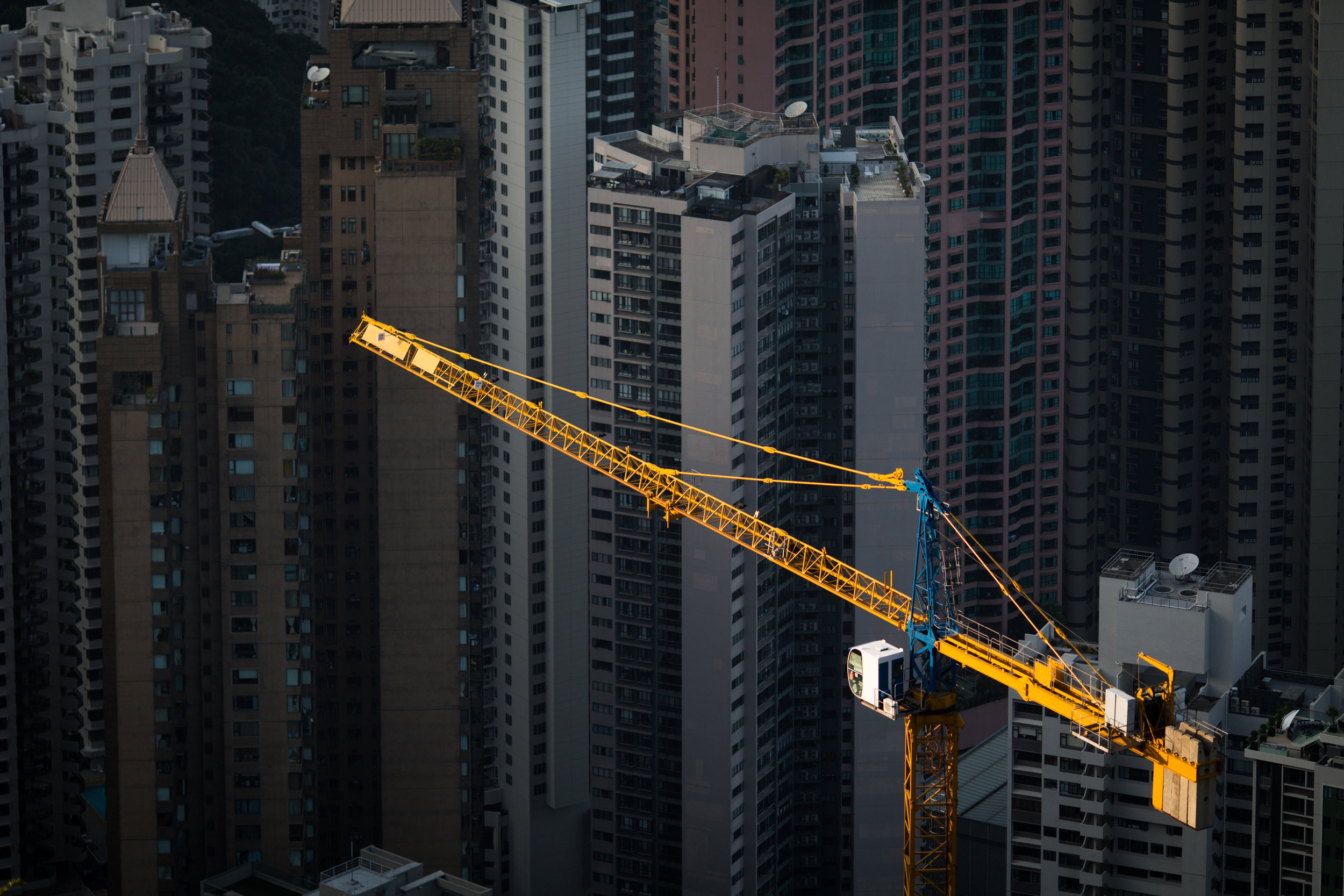 A yellow construction crane in sharp contrast to high rises below in Hong Kong