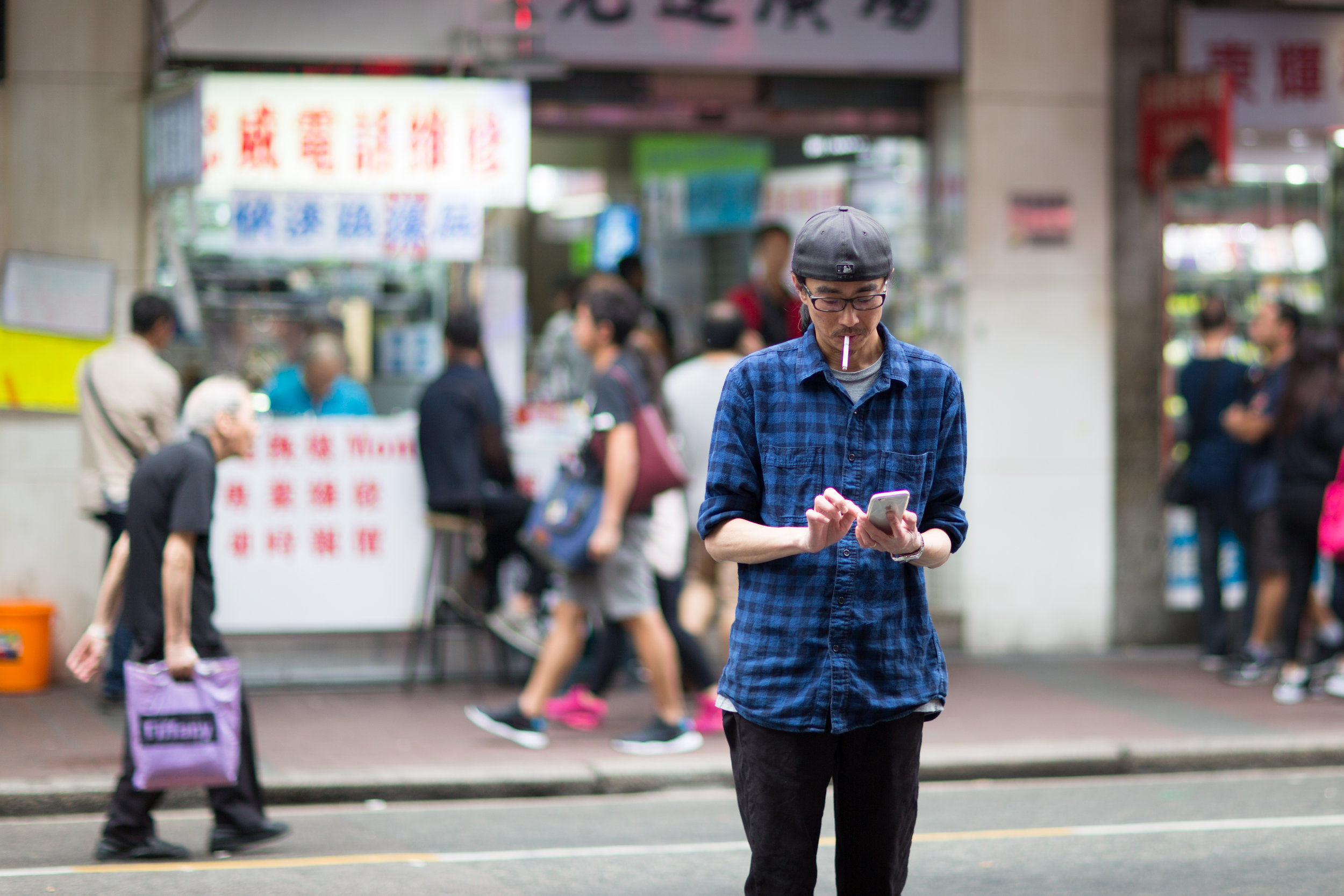 A man is surfing or texting on his mobile phone in Mongkok Hong Kong