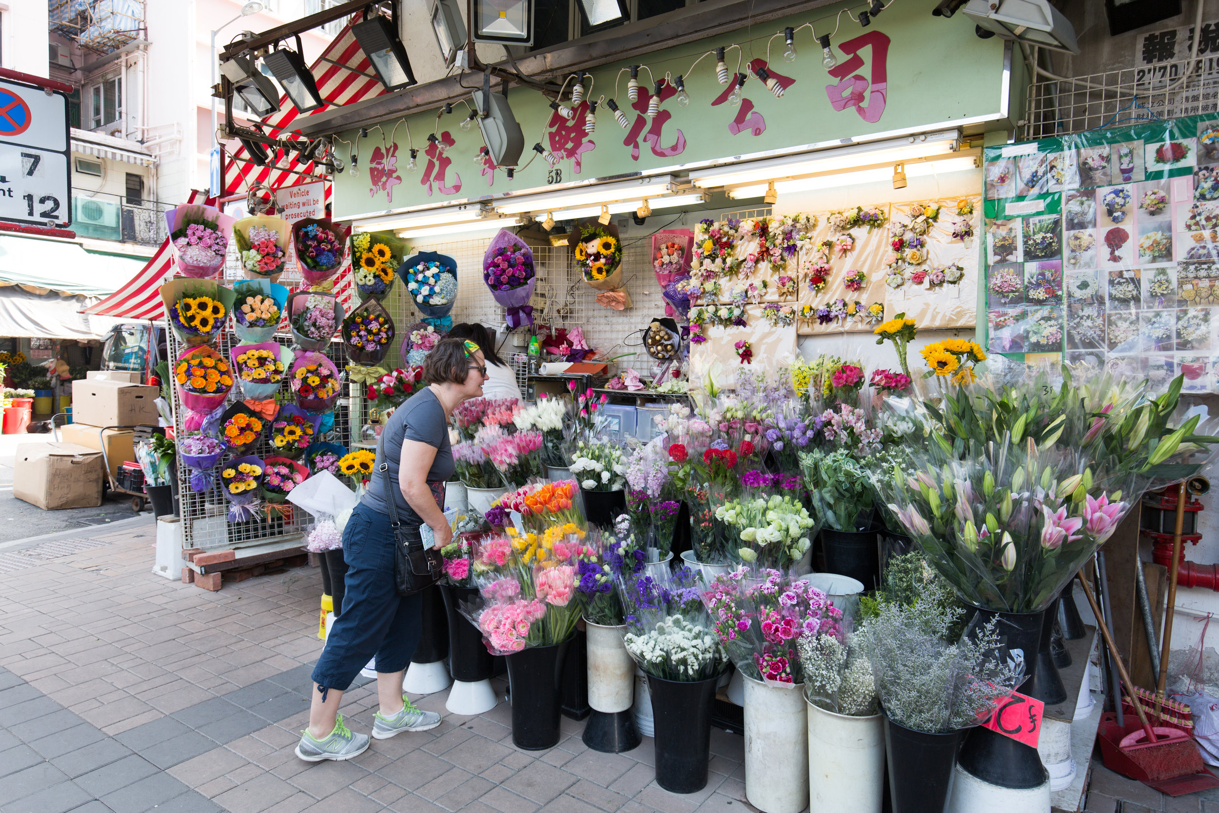A tourist stops to look at the many bouquets at a flower shop at the flower market in mongkok Hong Kong