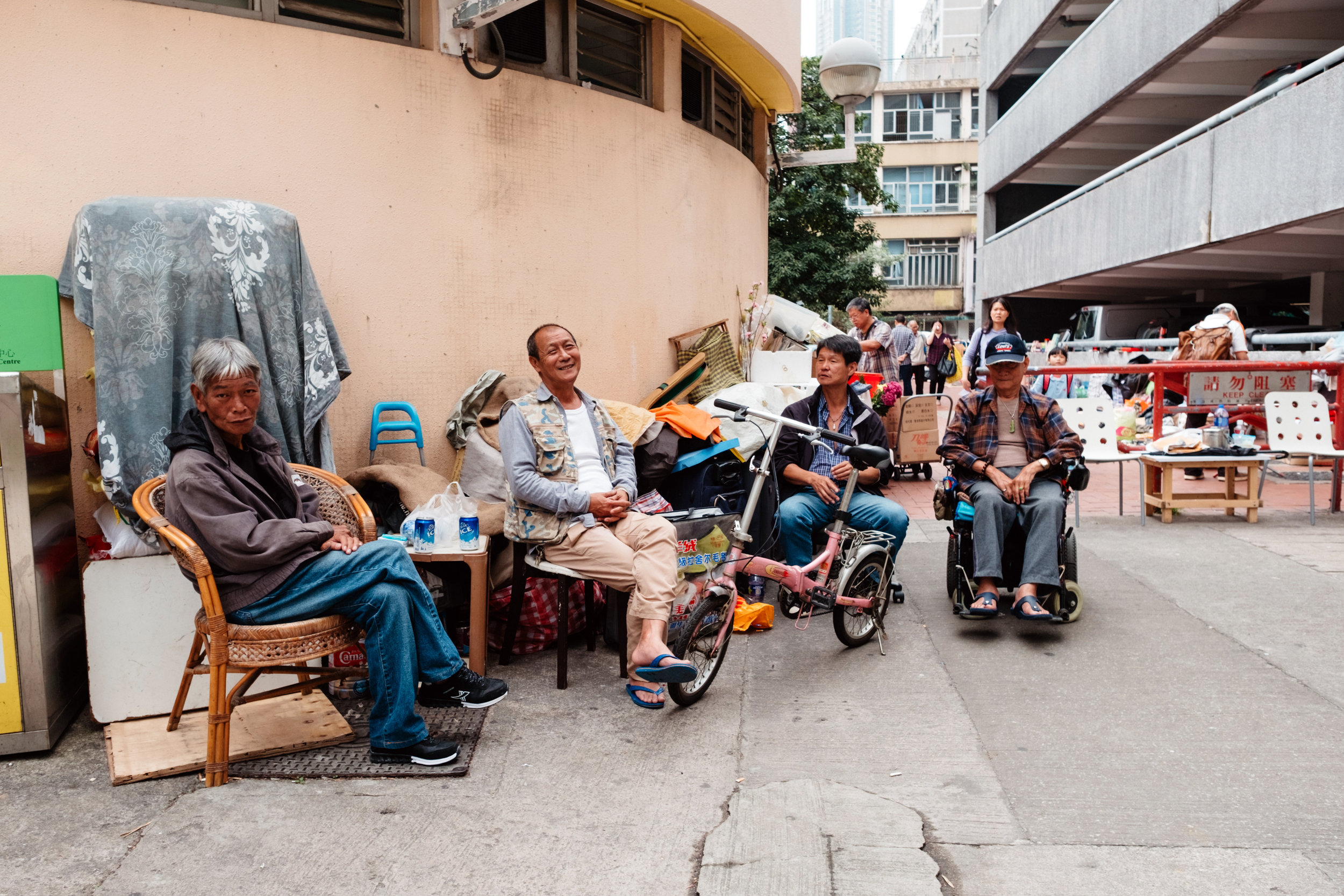 Four men join each other for a drink in a Kowloon Hong Kong back alley in a residential area