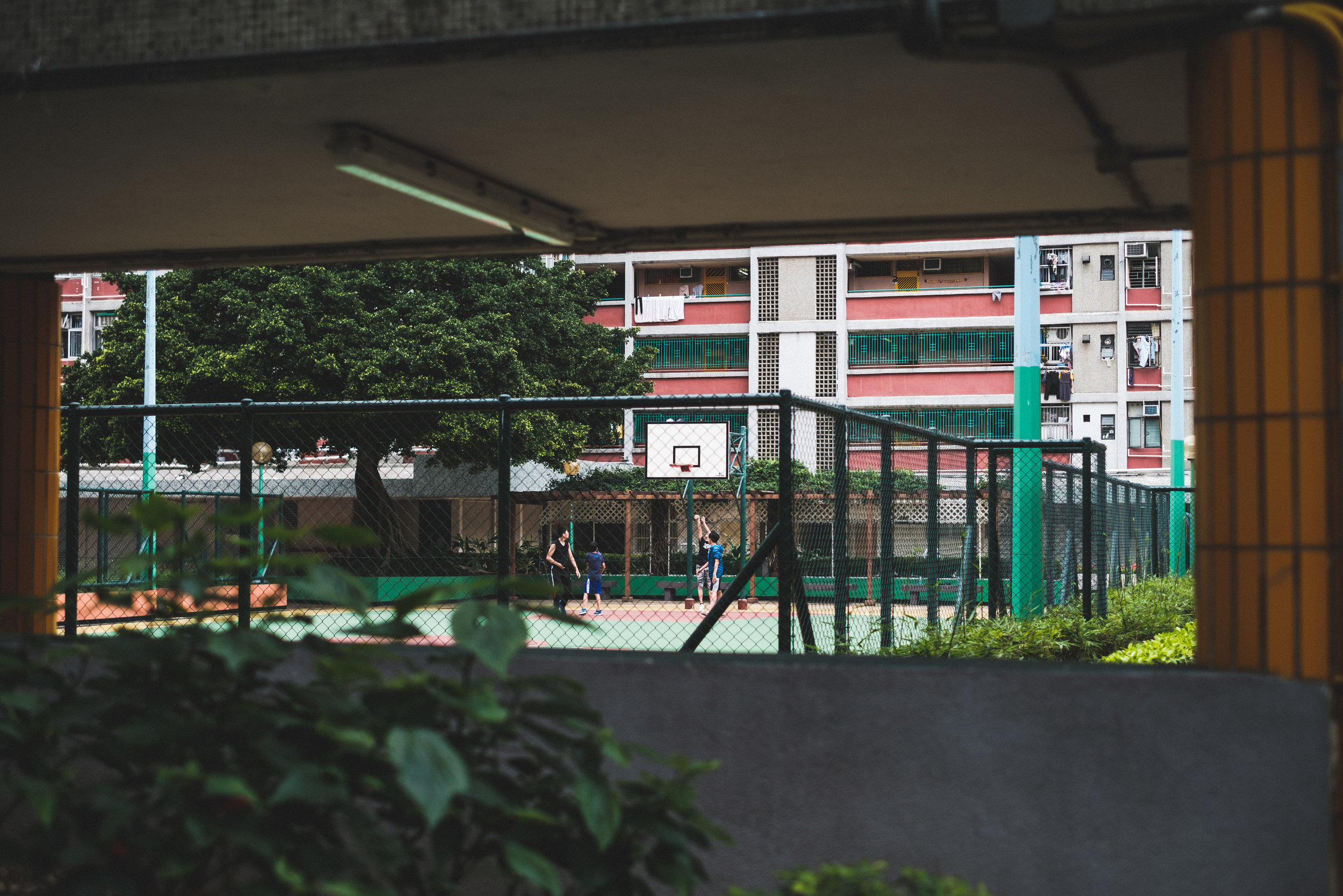 A group of young boys are having a game of basketball on city court in Kowloon Hong Kong residential area.