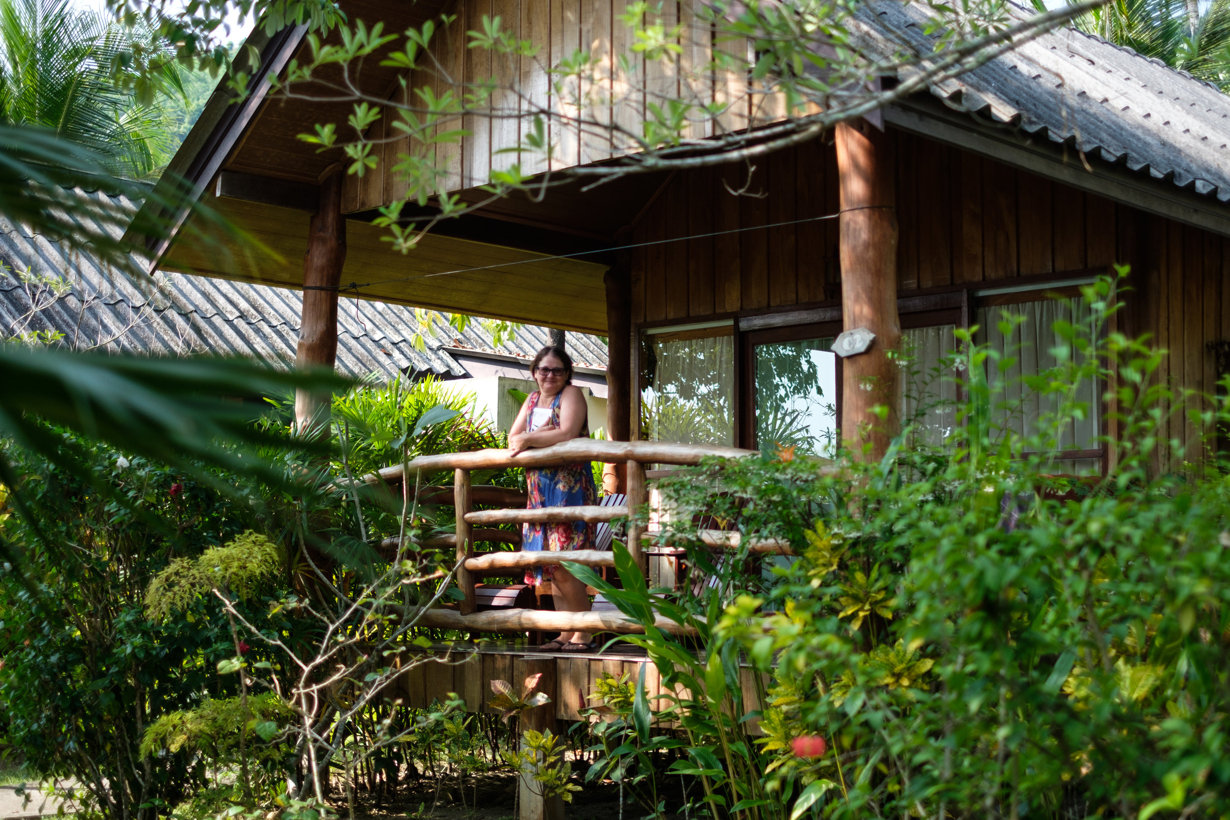 A woman stands or the porch of a private bungalow at The Thiwson Beach Resort at Koh Yao Yai in Thailand