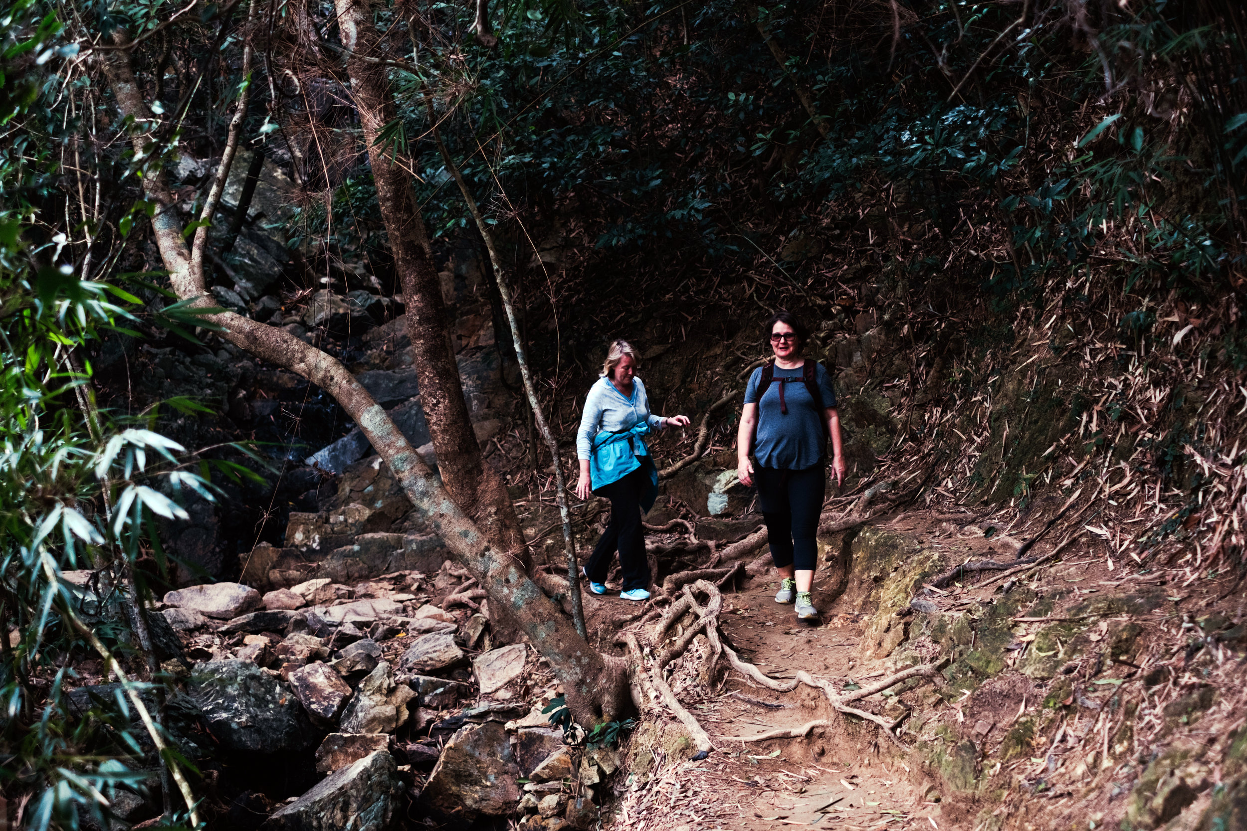 two middle aged women hike the Dragon's Back Trail in Hong Kong
