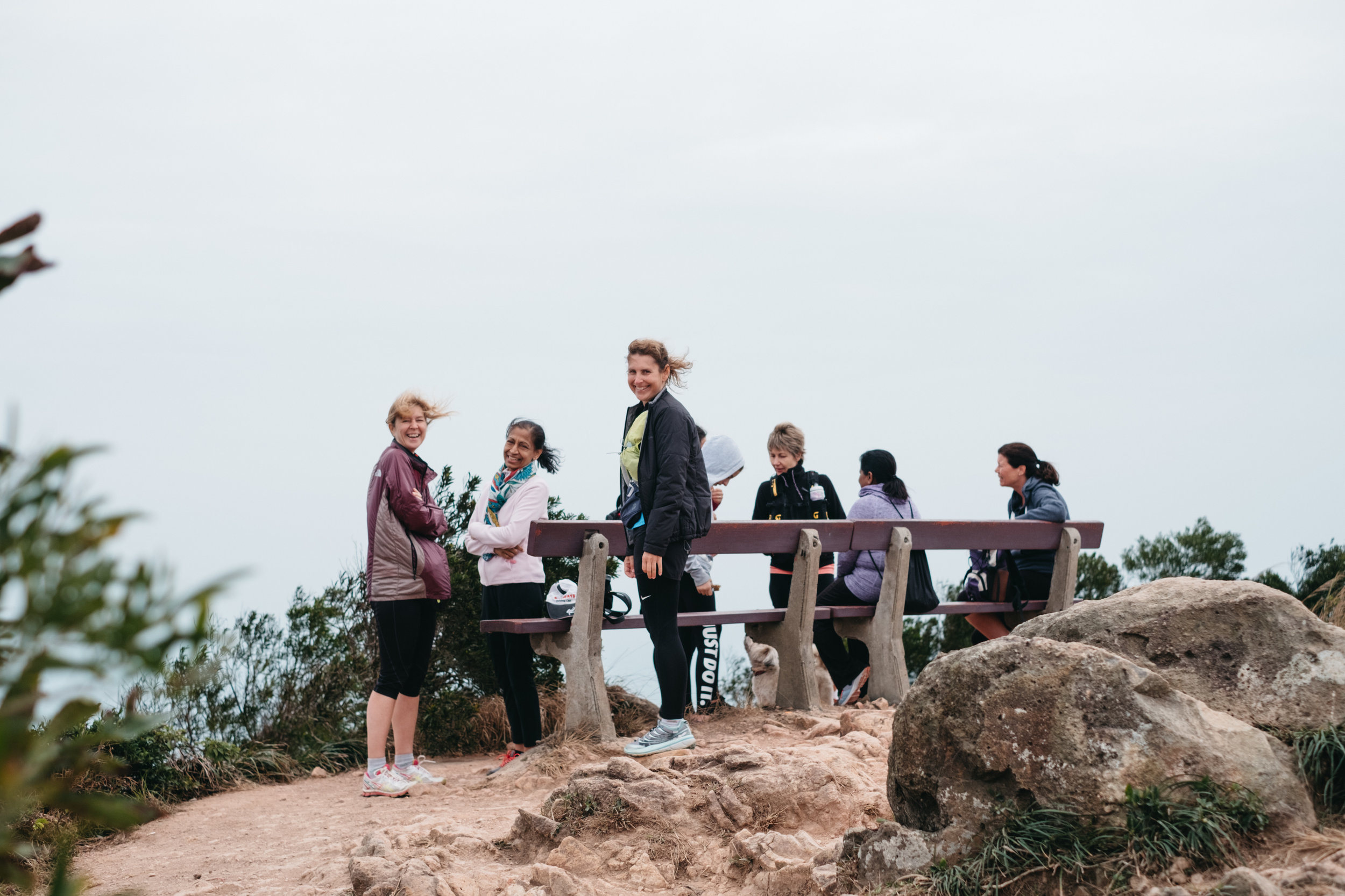 A group of women hikers stop at the top of the Dragon's Back Trail in Hong Kong for a rest