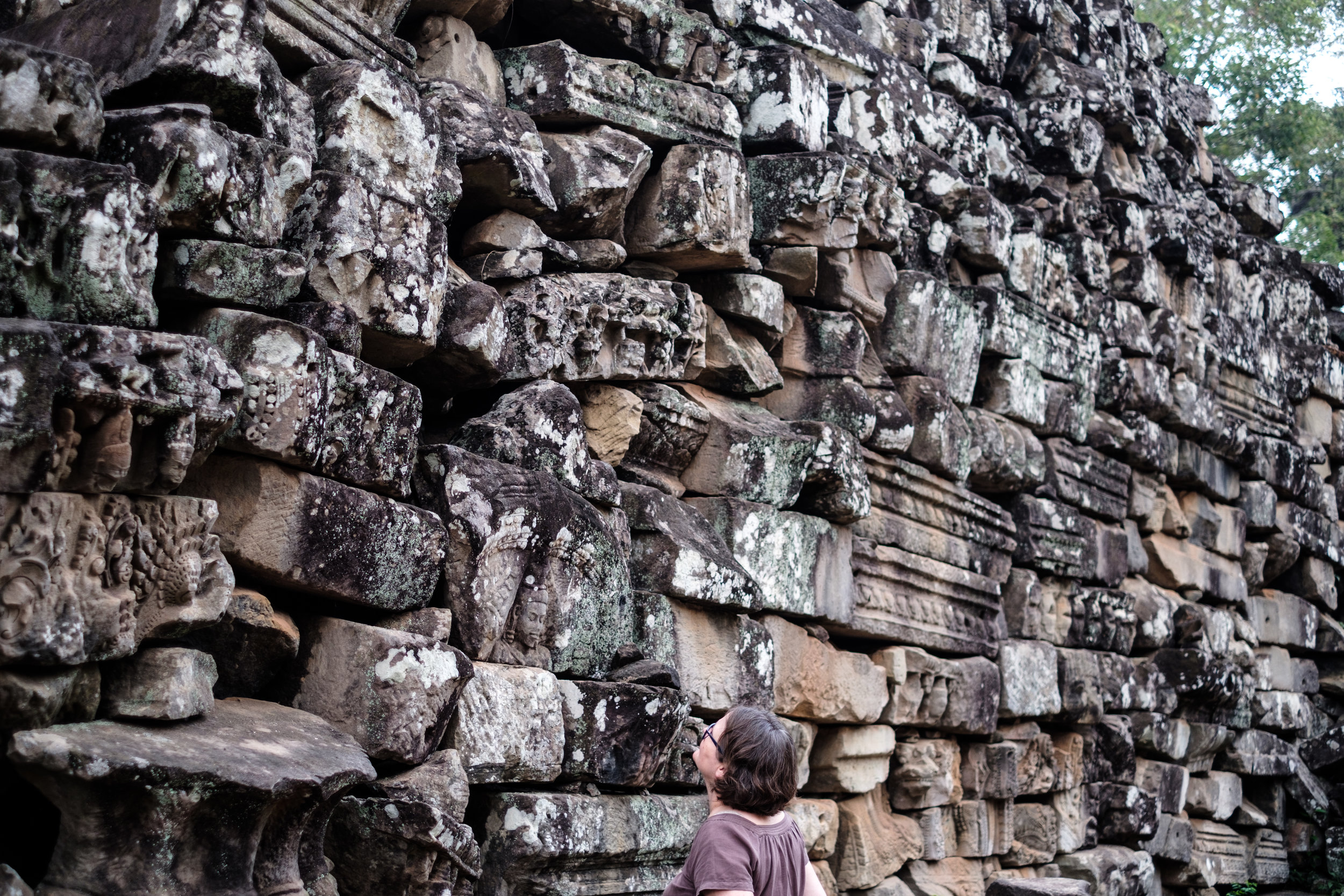 A woman studying the artifacts a Angkor Wat in Siem Reap