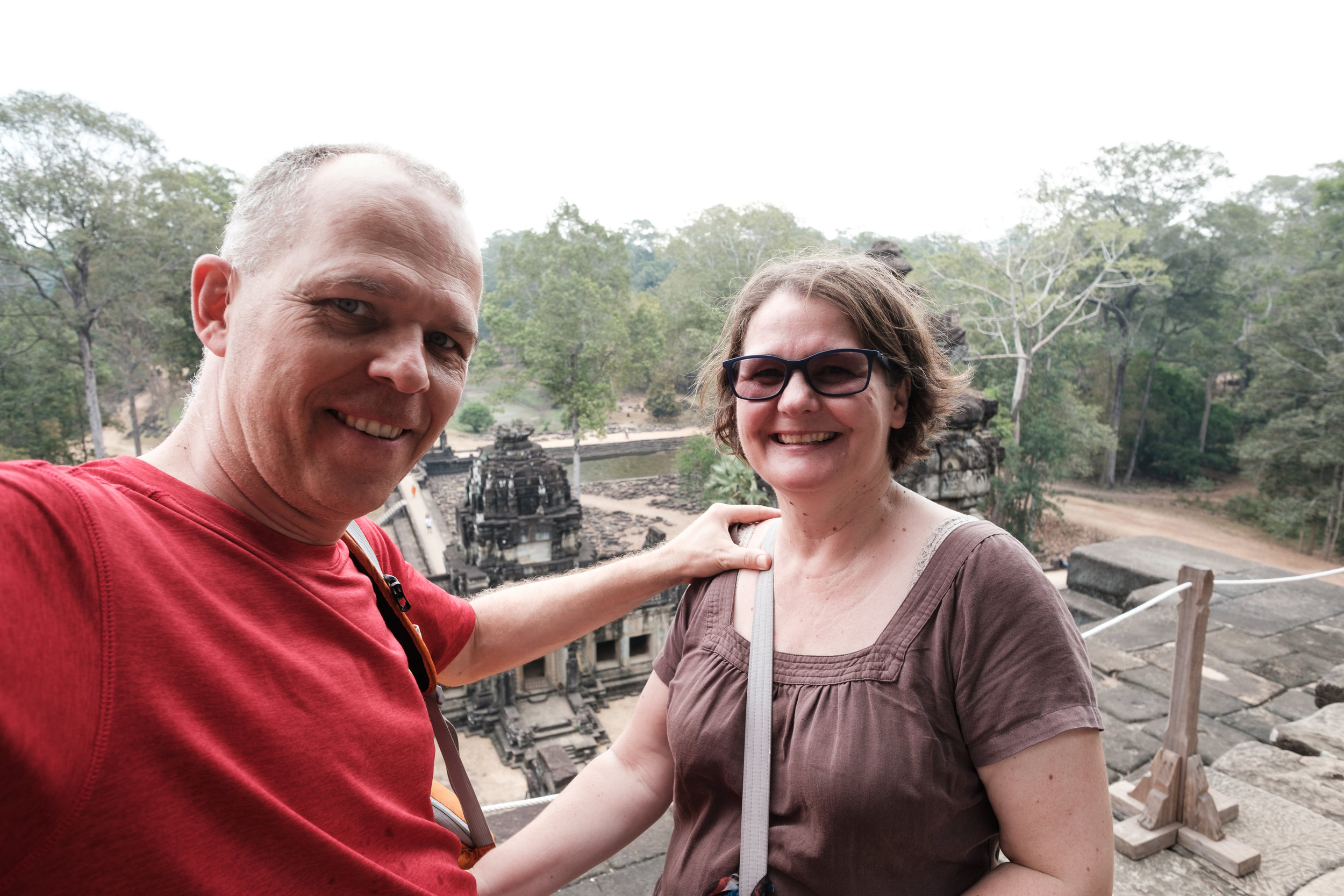 A middle aged couple smiles after climbing the stairs to the top of Angkor Wat in Siem Reap, Cambodia