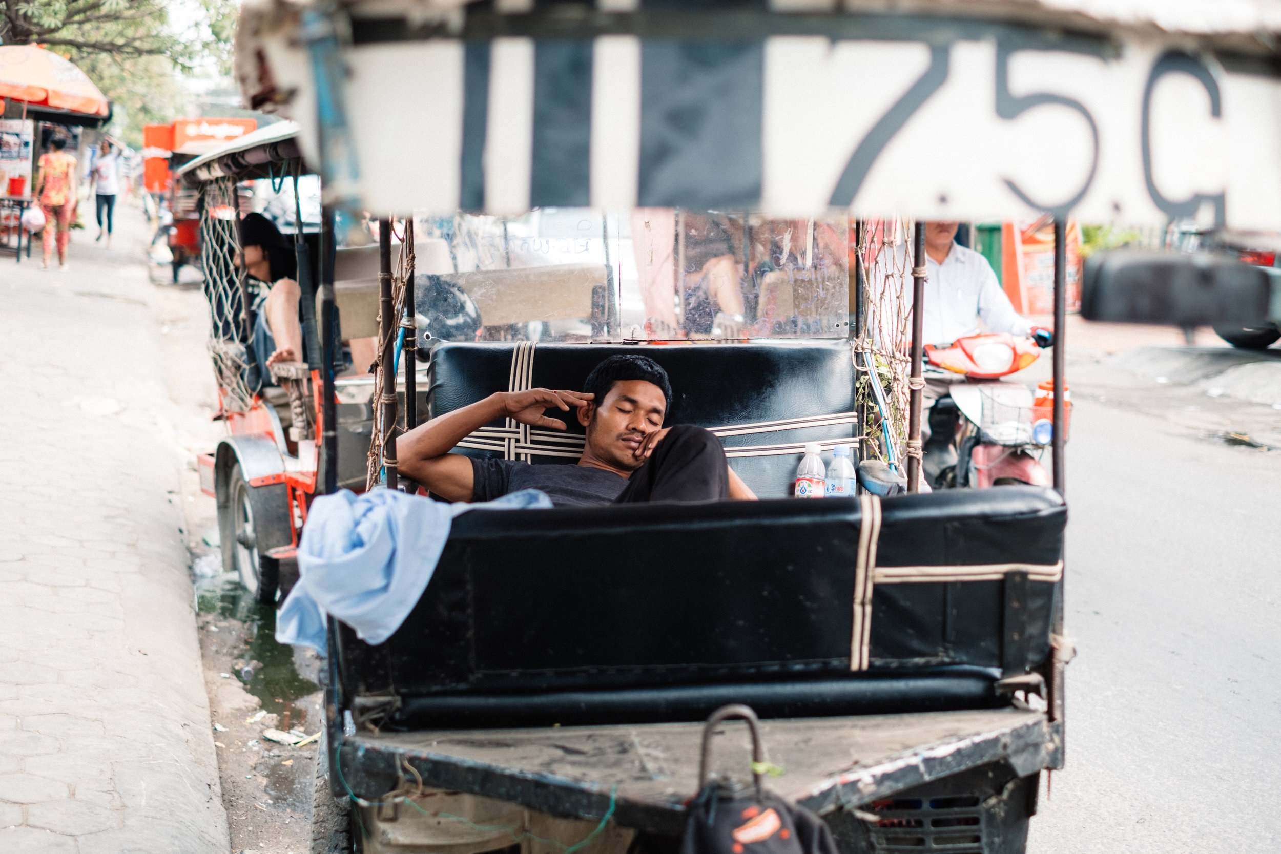 a man is having a nap in richshaw in the streets of Phnom Penh in Cambodia