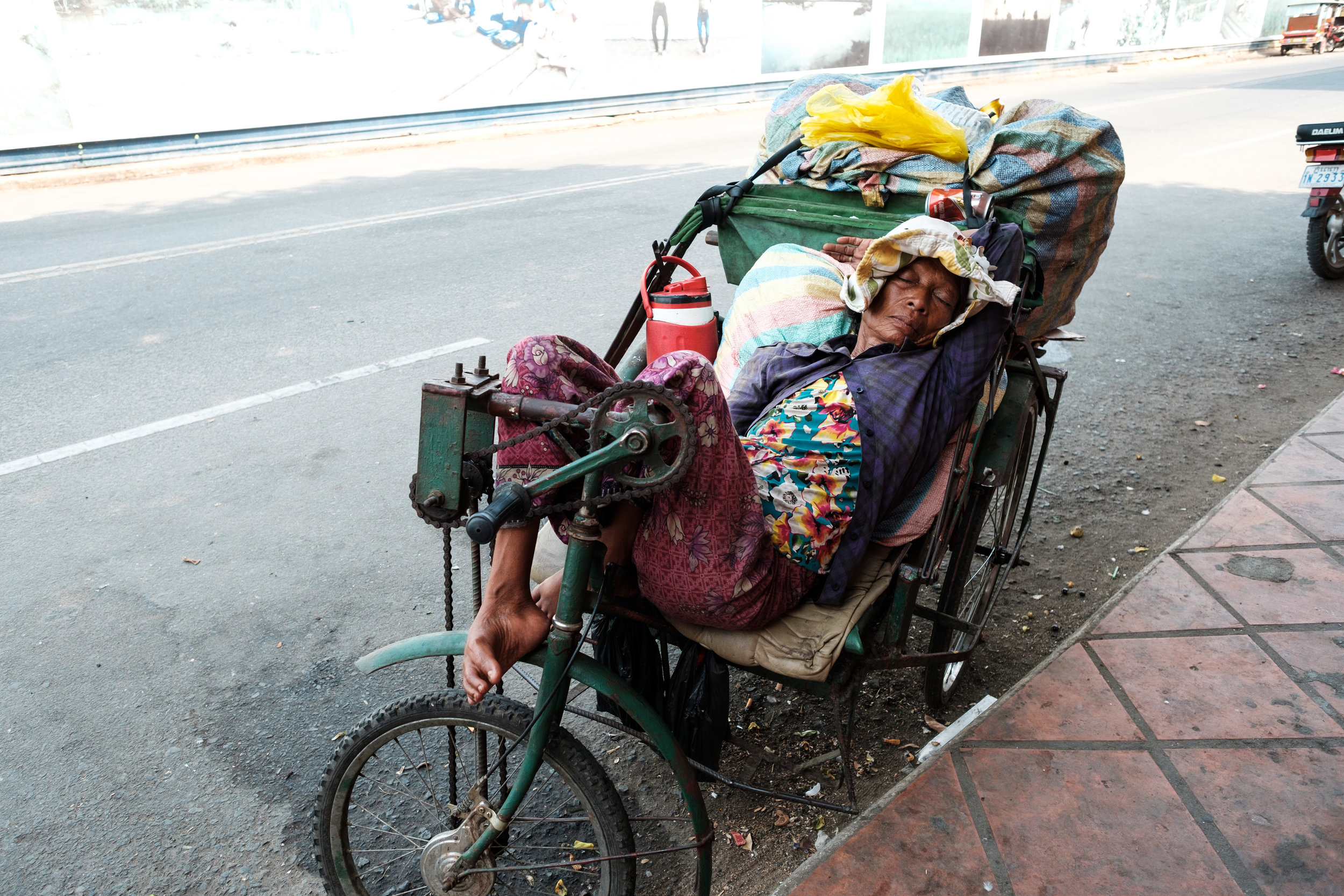 A elderly woman is having a nap on her rick shaw during the mid day heat in Phnom Penh Cambodia