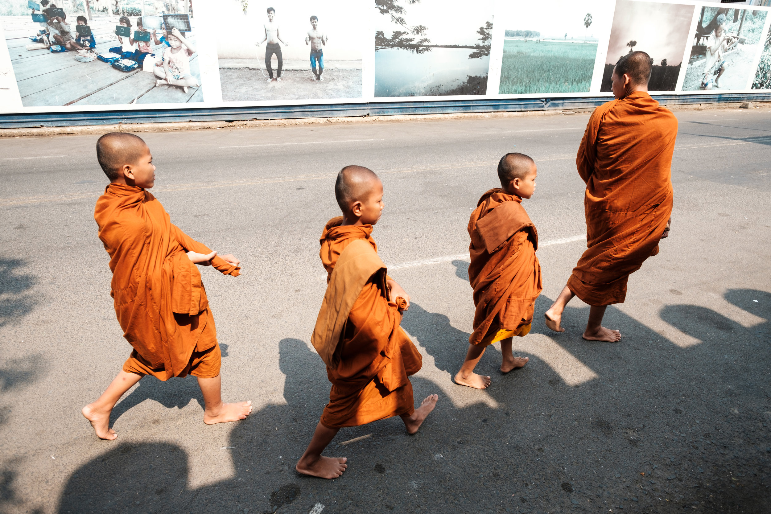Four monk in the classic orange gown walk through a street in Phnom Penh Cambodia