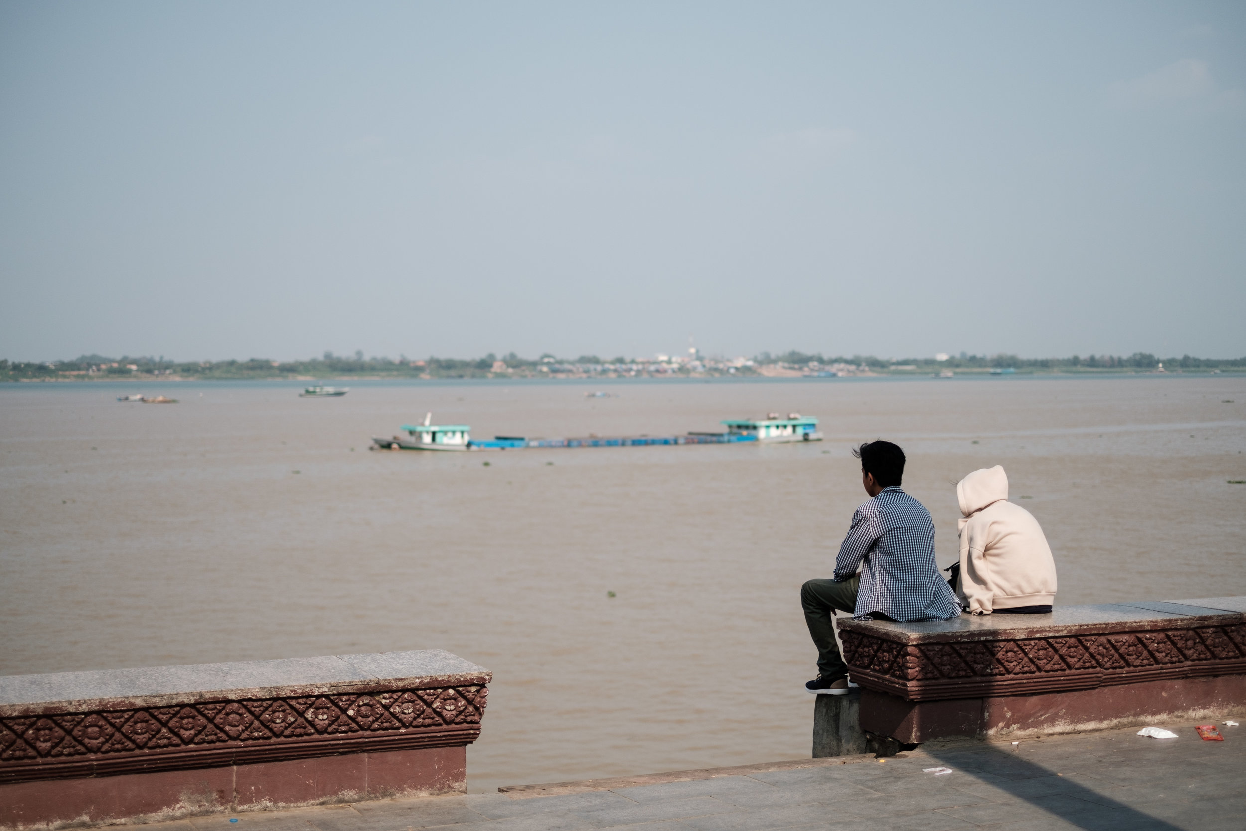 Two young people a gazing out at the Mekong River in Phnom Penh Cambodia