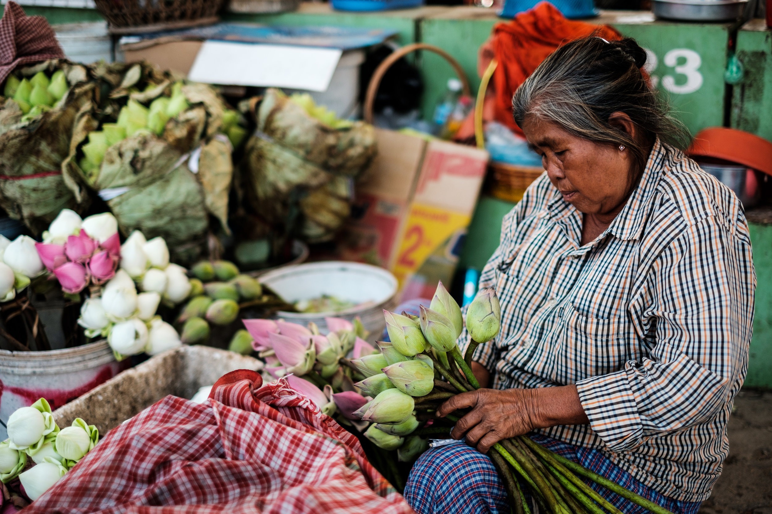 An elderly woman preps Flowers are prepped at a market in Phnom Penh Cambodia