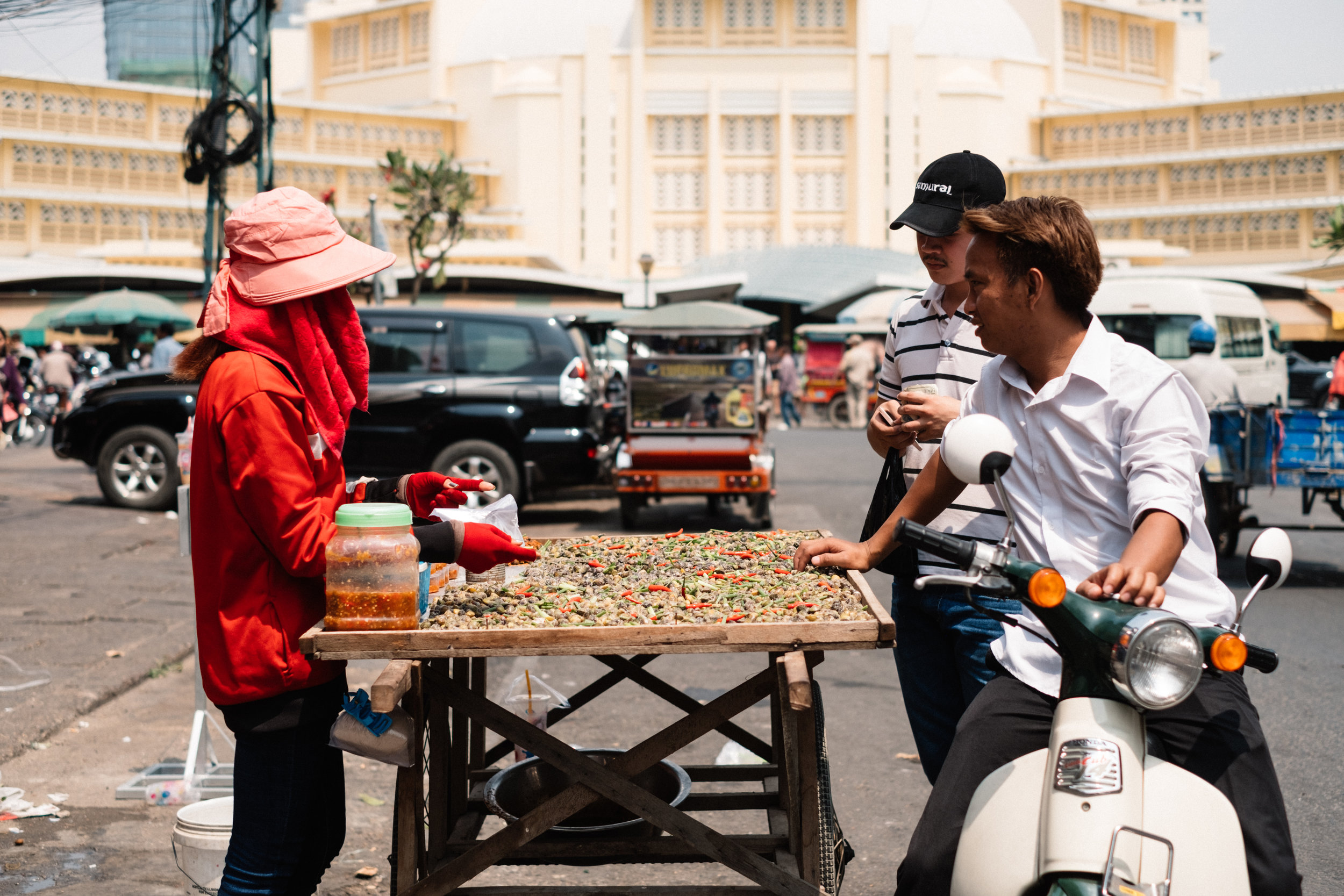 Two men stop by a street vendor in Phnom Penh Cambodia to check out the goods