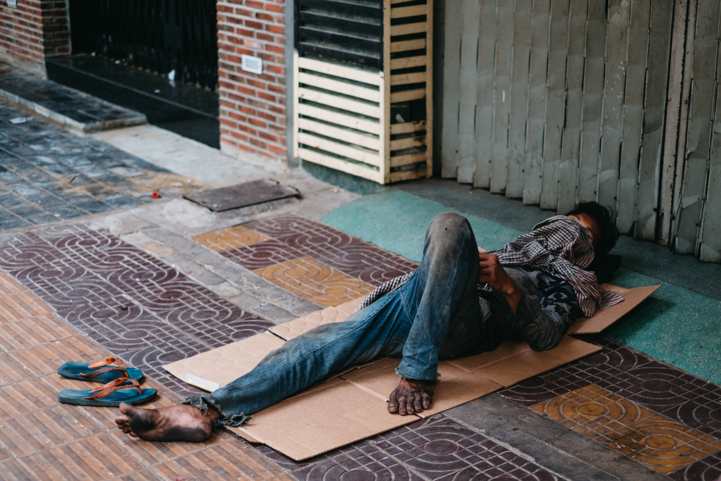 A homeless man is sleeping on the sidewalk on a piece of cardboard in Phnom Penh Cambodia
