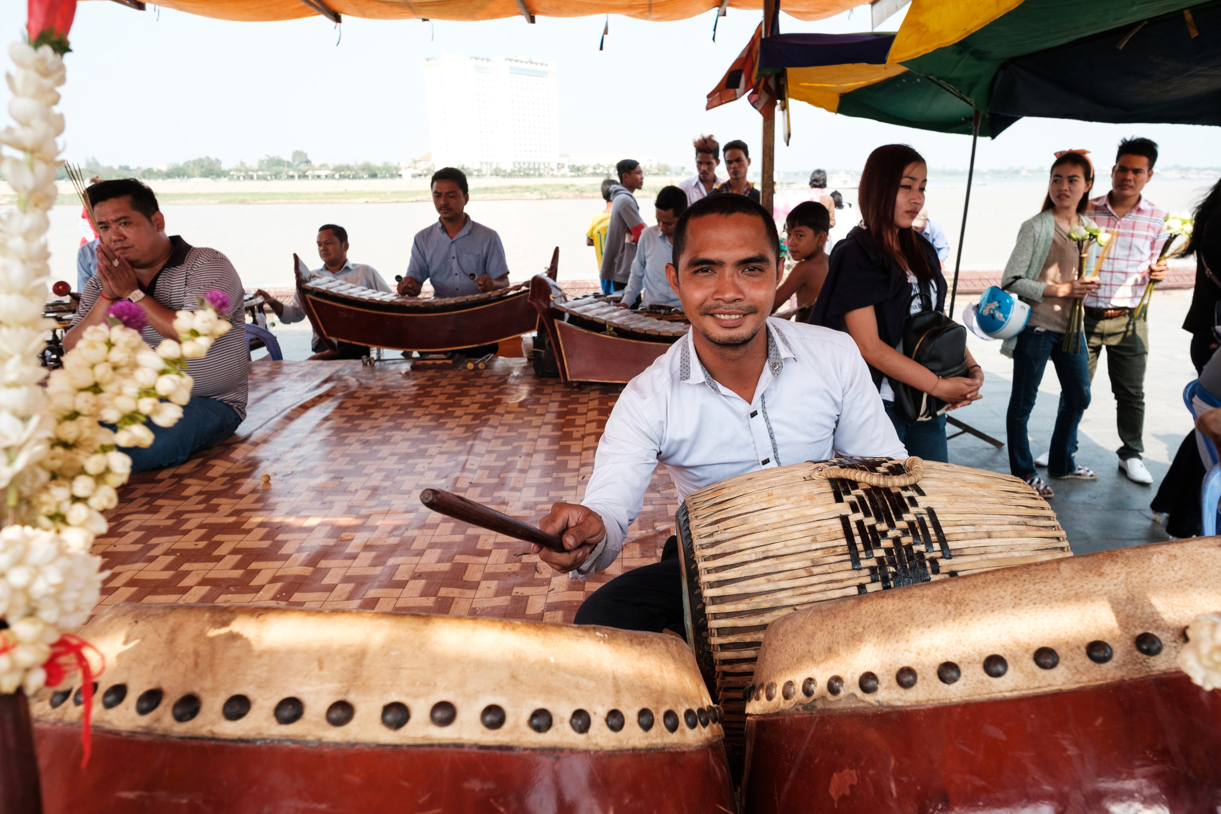 A drummer is part of a ceremony giving offerings to buddha in Phnom Penh Cambodia