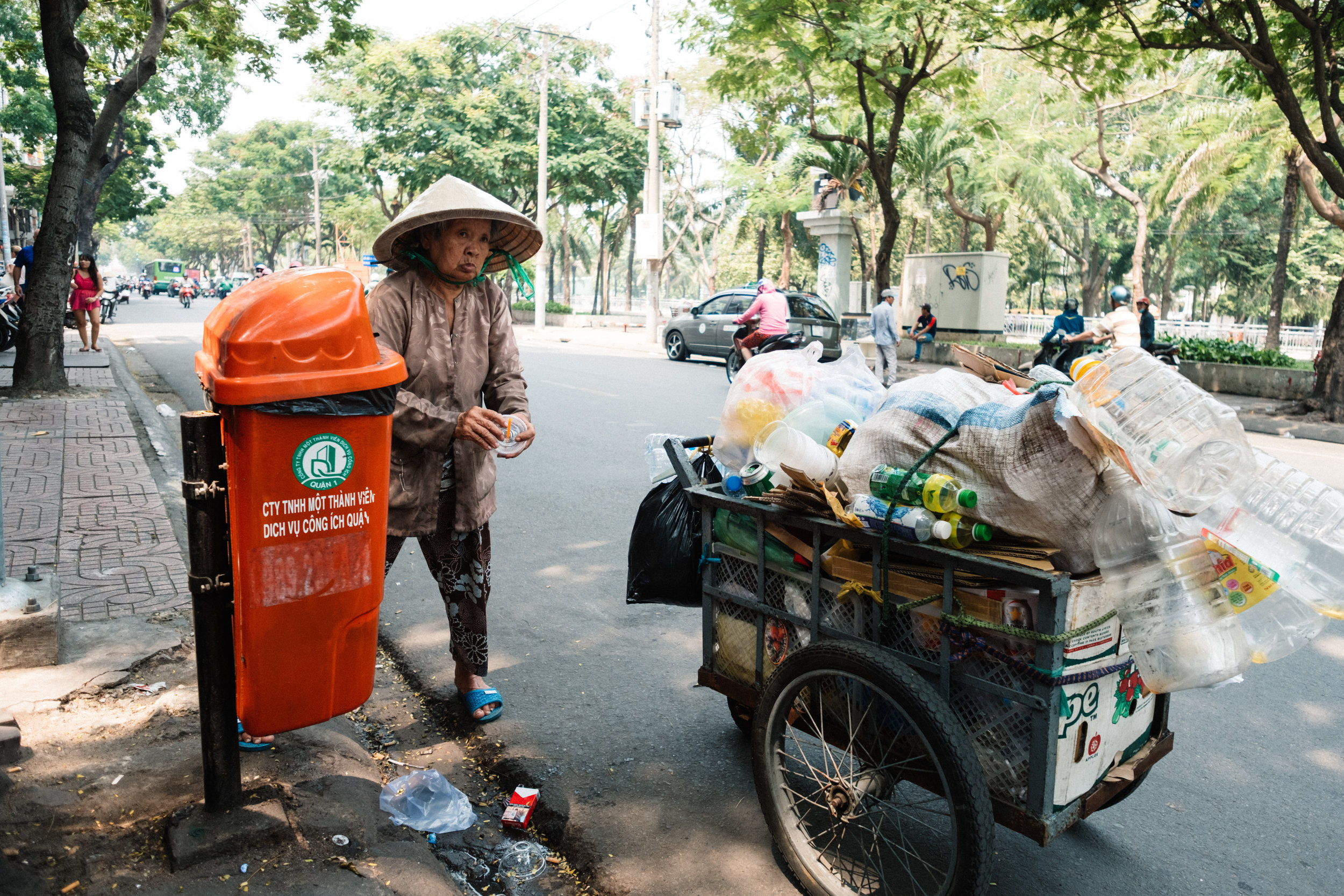 An elderly woman is collecting empties from a garbage bin