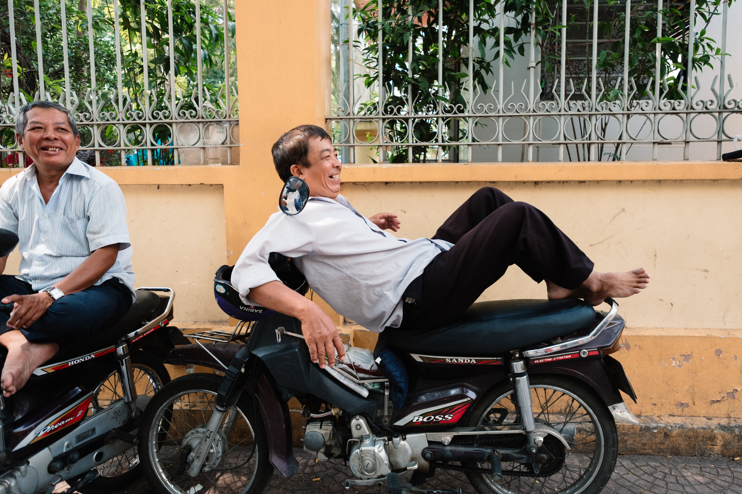 A couple of men are having a rest on their motor cycles in Ho Chi Minh City, Vietnam