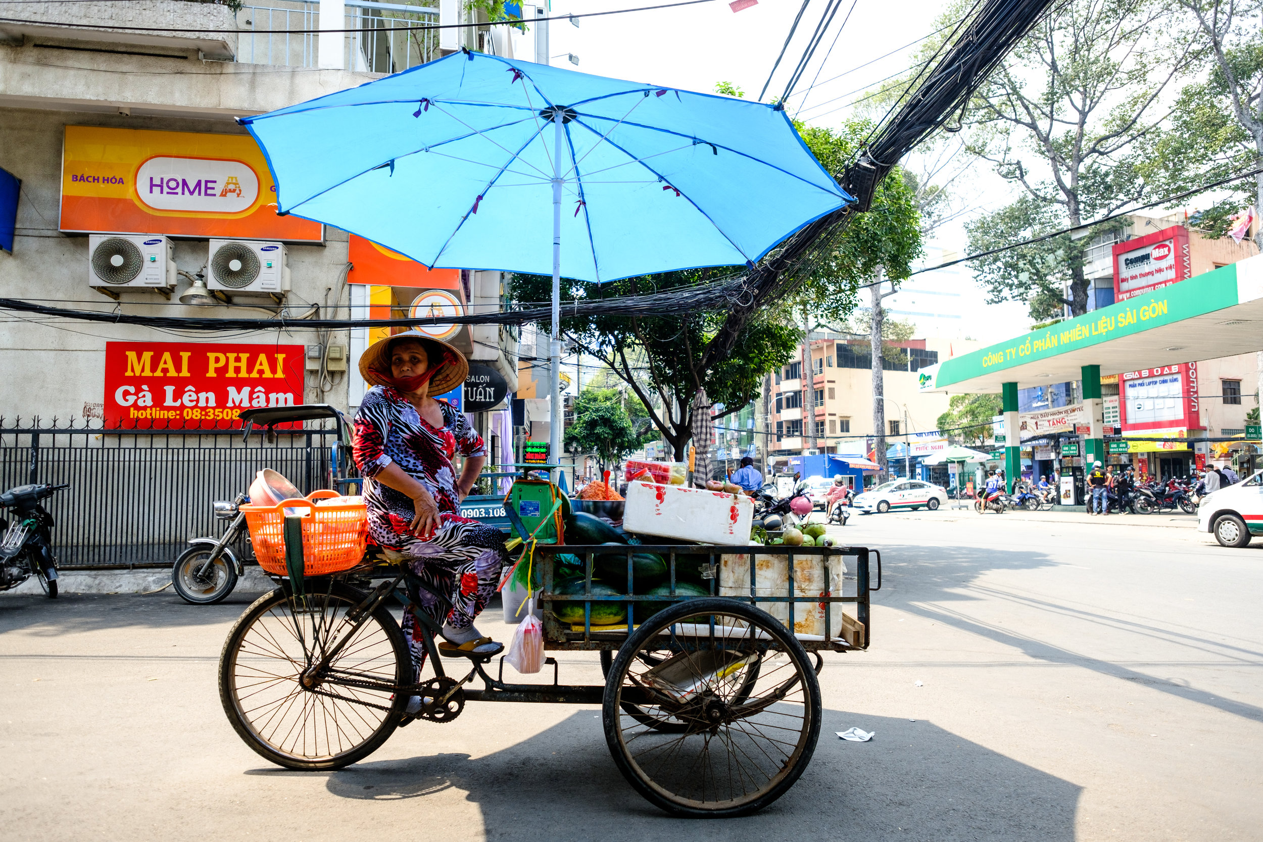 A street vendor sells vegetables from her tricycle store in Ho Chi Minh City, Vietnam
