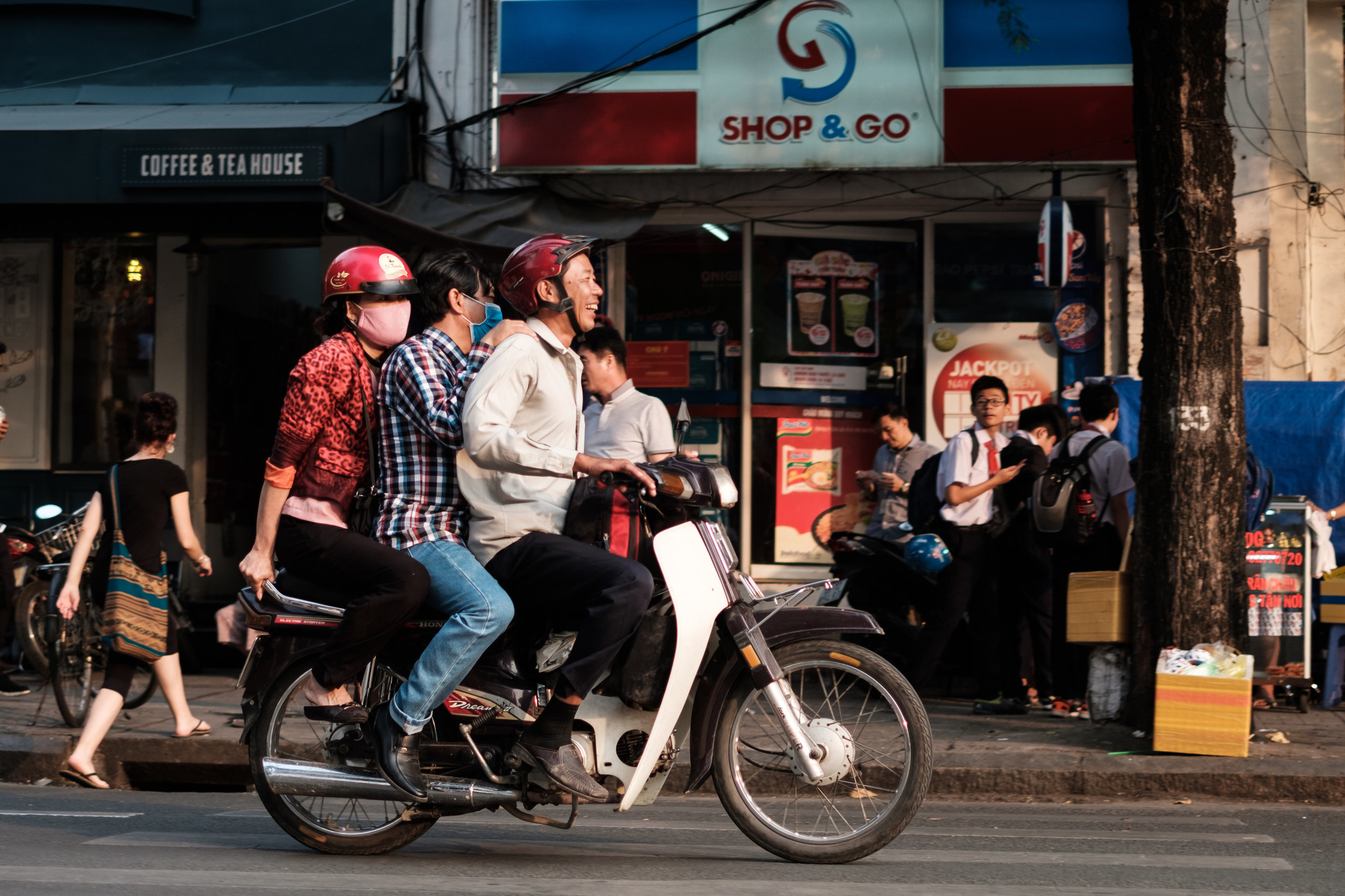 Three people on a scooter ride by a shop & go store in Ho Chi Minh City, Vietnam