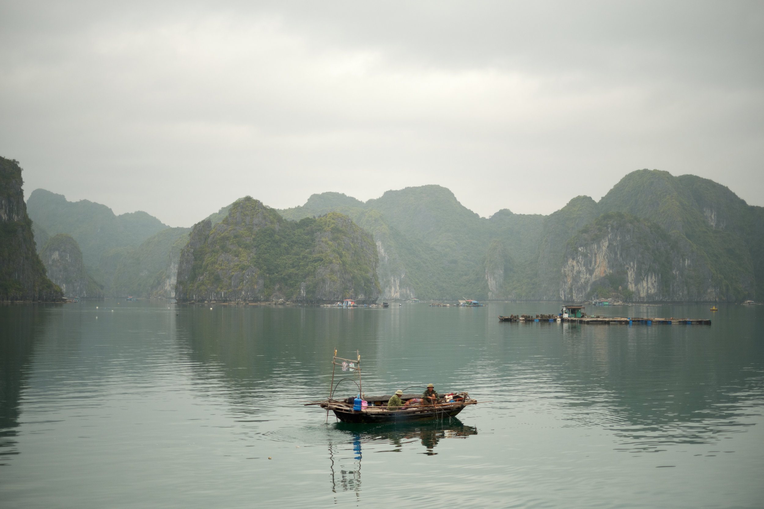 Two men working from their fishing boat near a floating village on Lan Ha Bay.