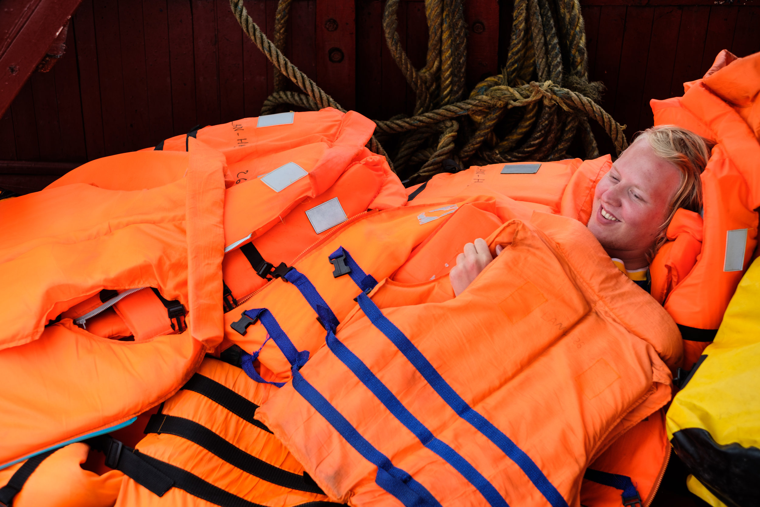 A Norwegian traveler takes a rest under the life jacket on a vessel during a cruise on Lan Ha Bay in Vietnam
