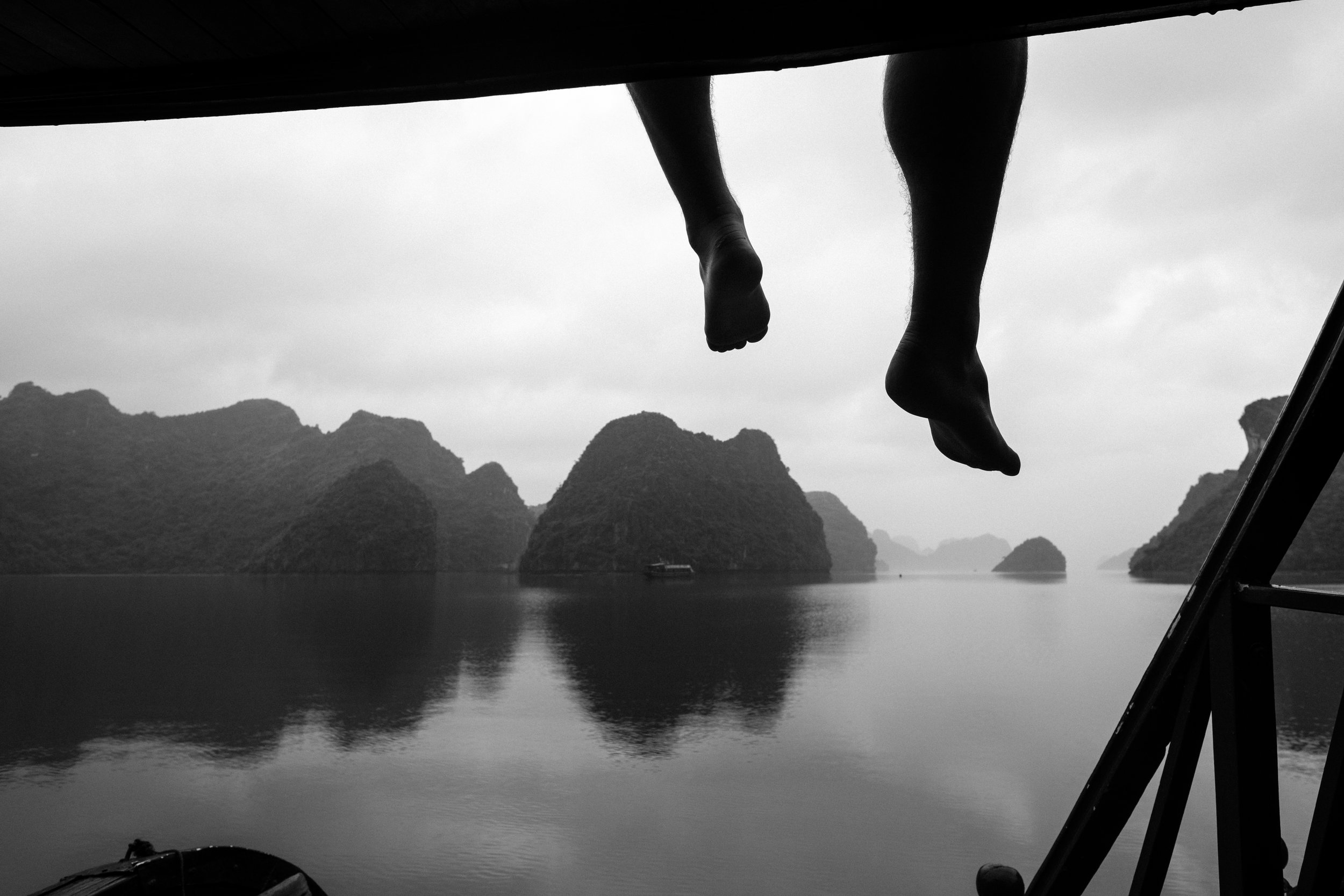 A travels rest with his feet hanging over the edge of a vessel during a cruise of Lan Ha Bay in Vietnam