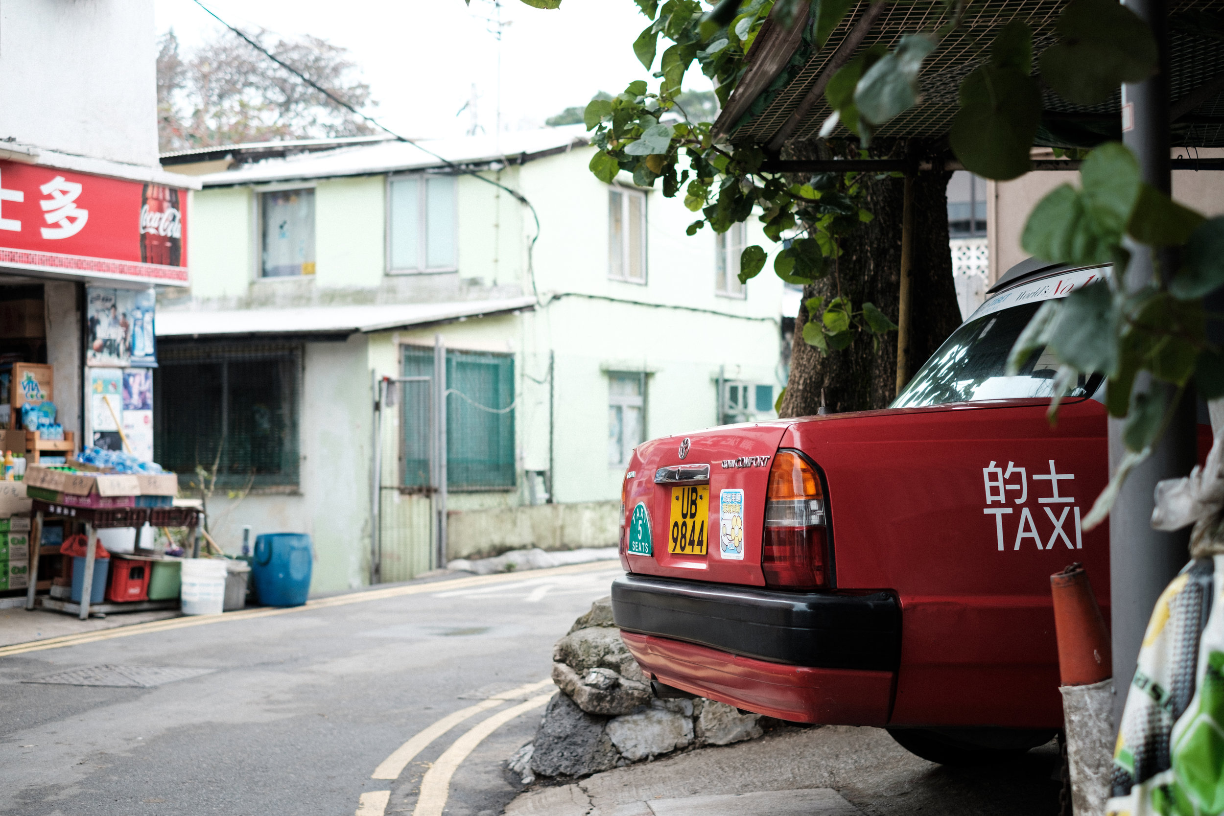 A classic red hong kong cab is parked in a garage in Shek O