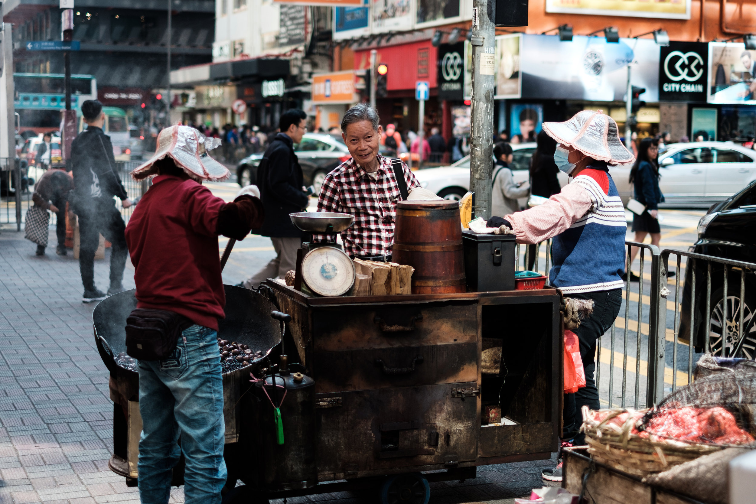 A group of people gather around a food vendor in Causeway Bay, Hong Kong