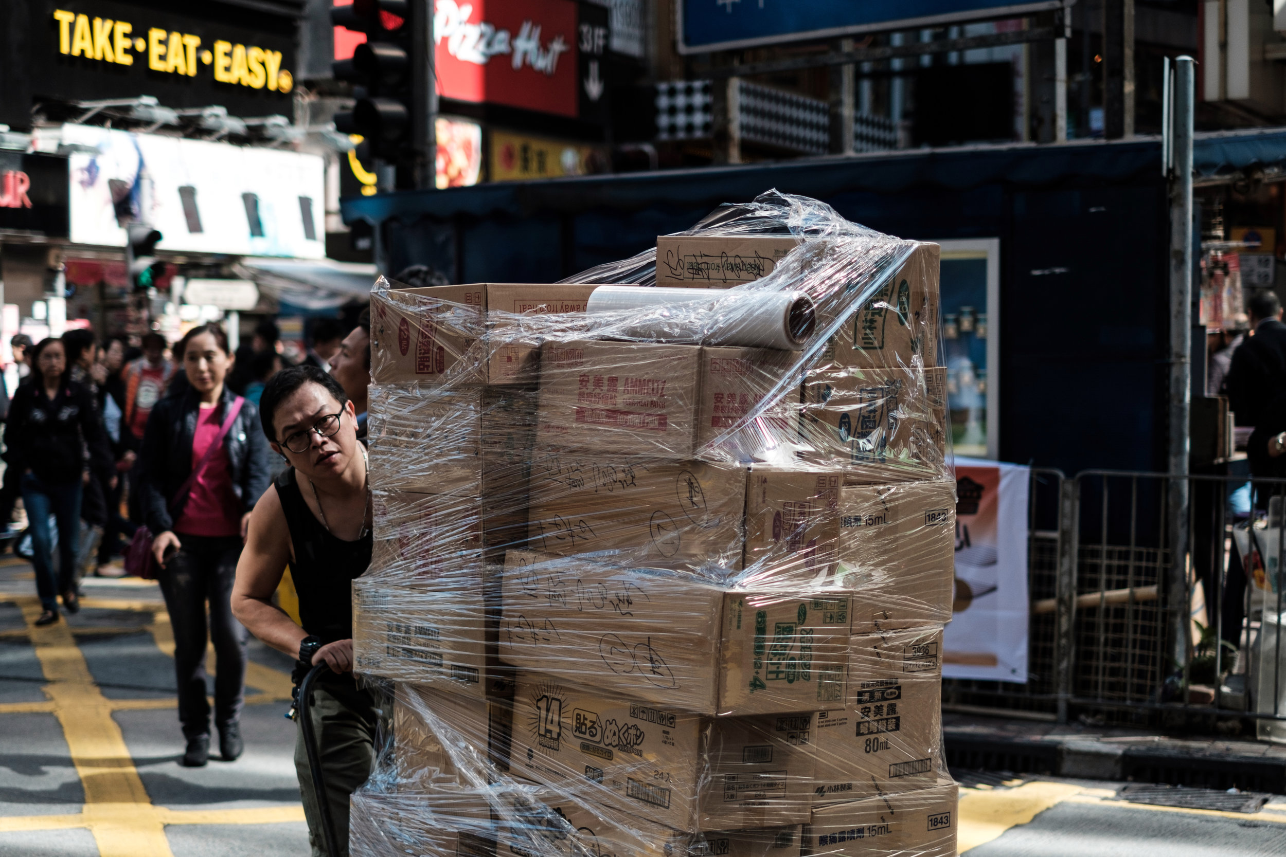 A man walk over a cross walk in Causway Bay with a big pallet of plastic wrapped good in Hong Kong