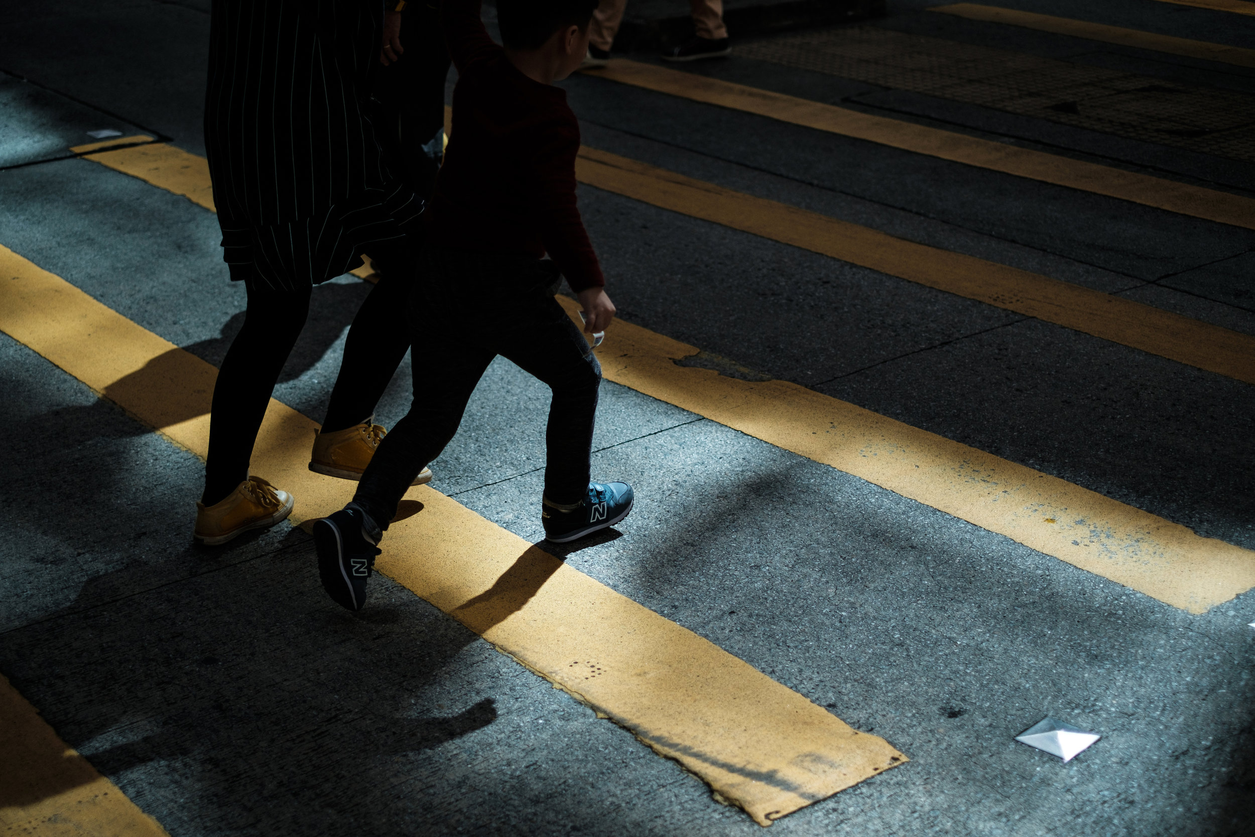 Two people in silhouette at a yellow cross walk in Causeway Bay Hong Kong
