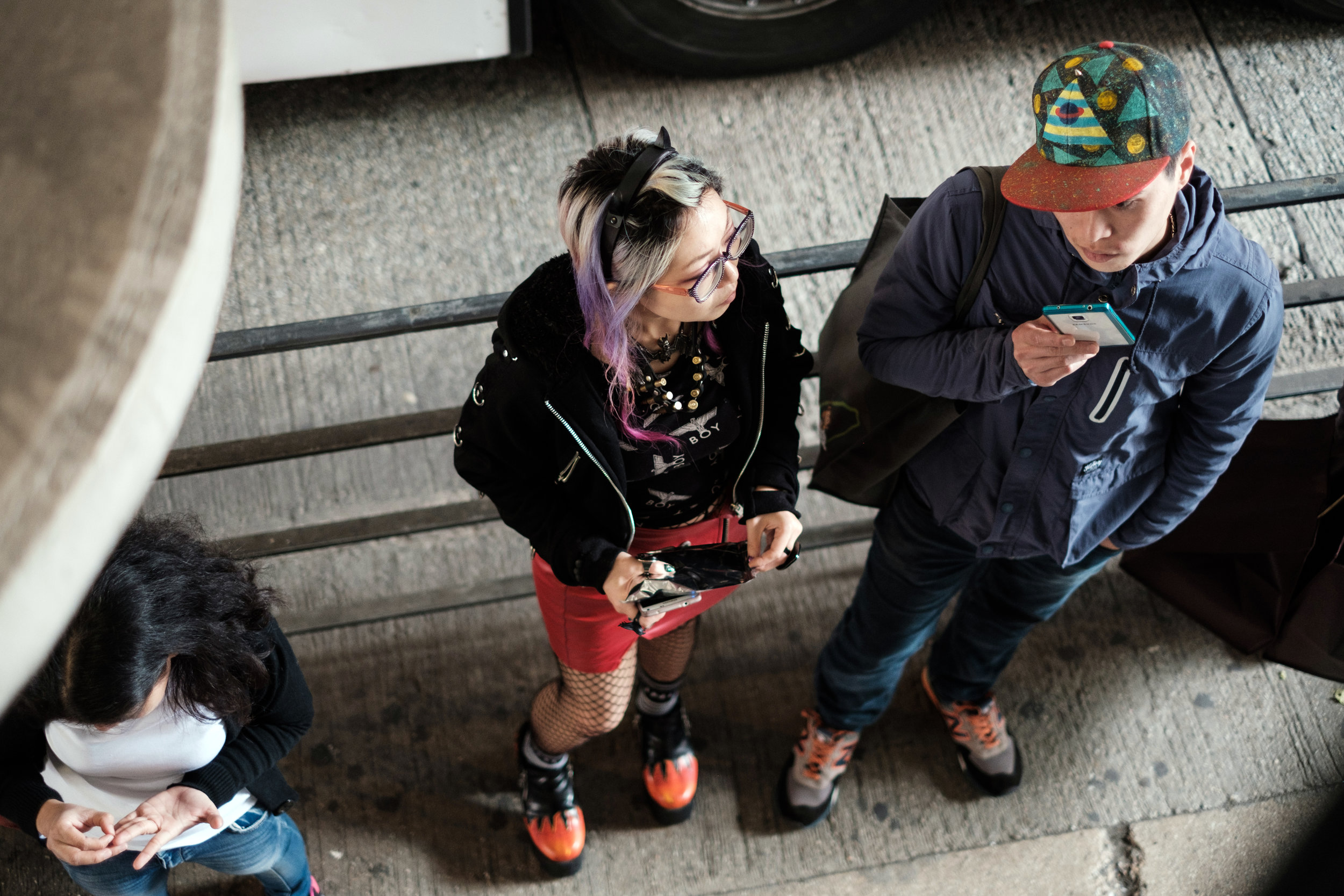 A young couple on their smart phone is waiting for a tram in Wan Chai Hong Kong