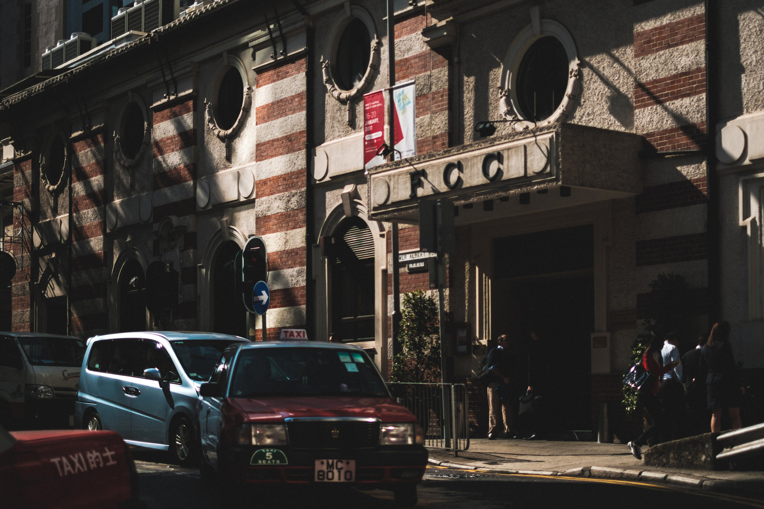 A red cab pulls out from the FCC, the Foreign Correspondence Club in Hong Kong