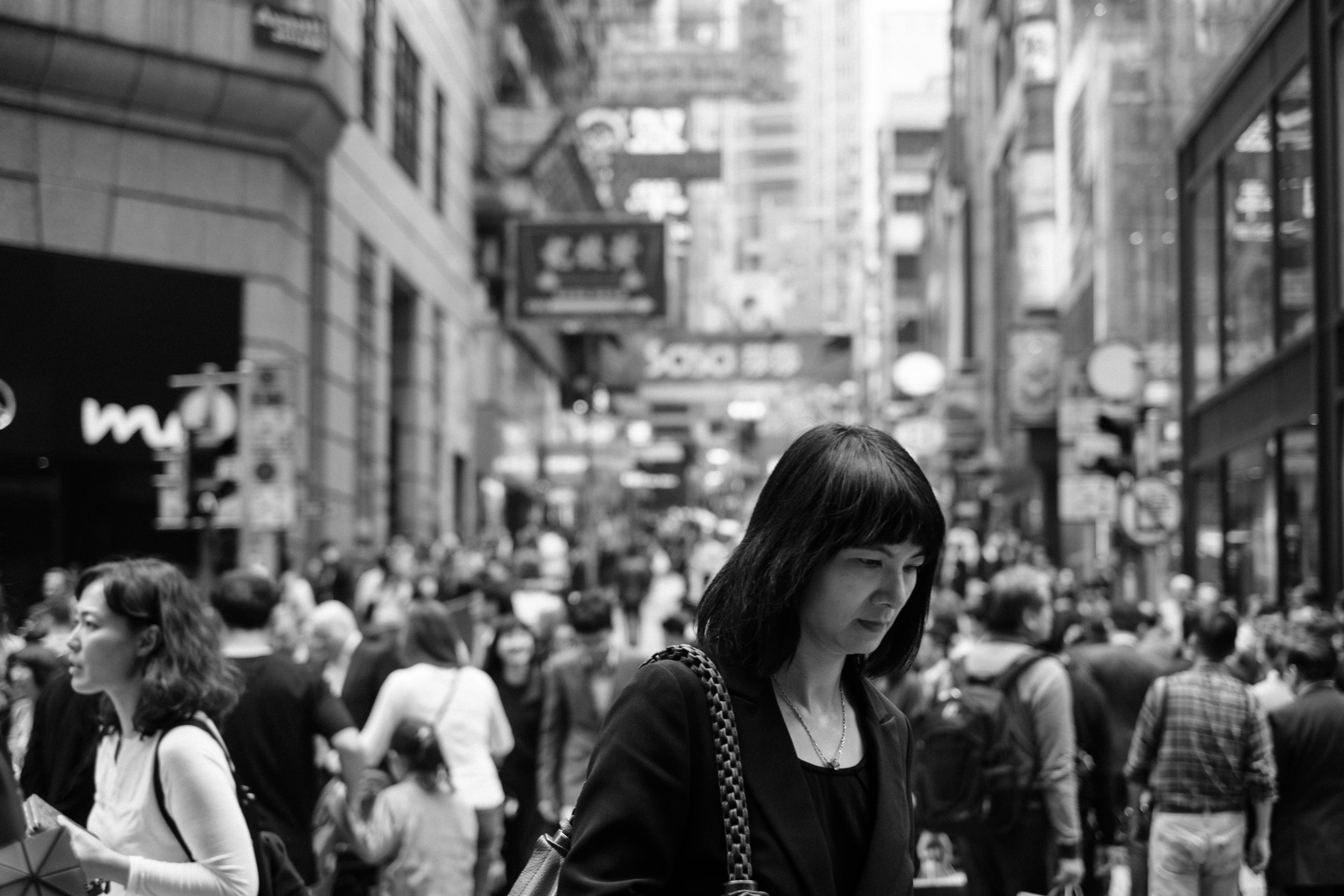 A woman crosses the street in the crowded Hong Kong Central district
