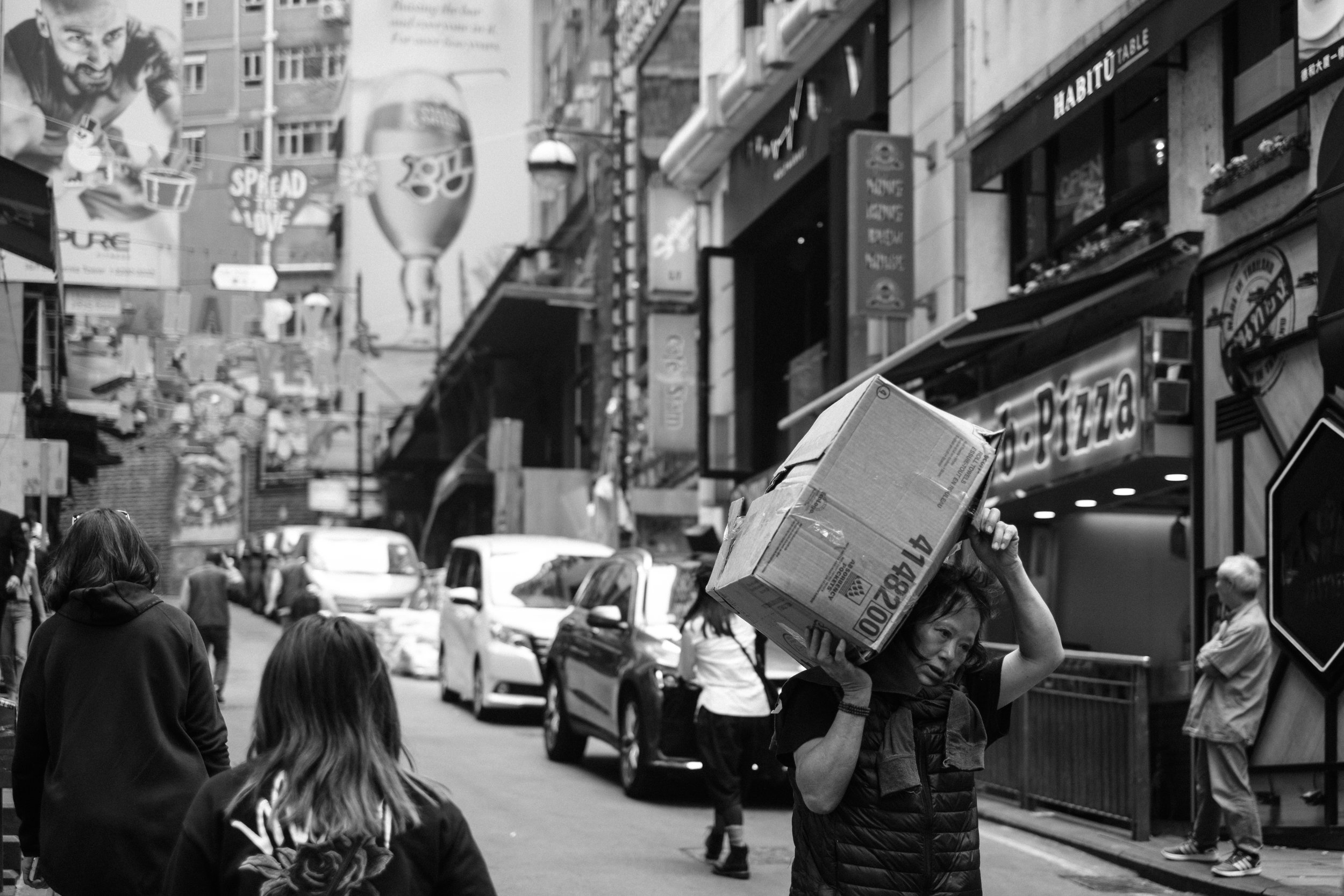 A woman carries a cardboard box on her shoulder through a street in the Central district of Hong Kong