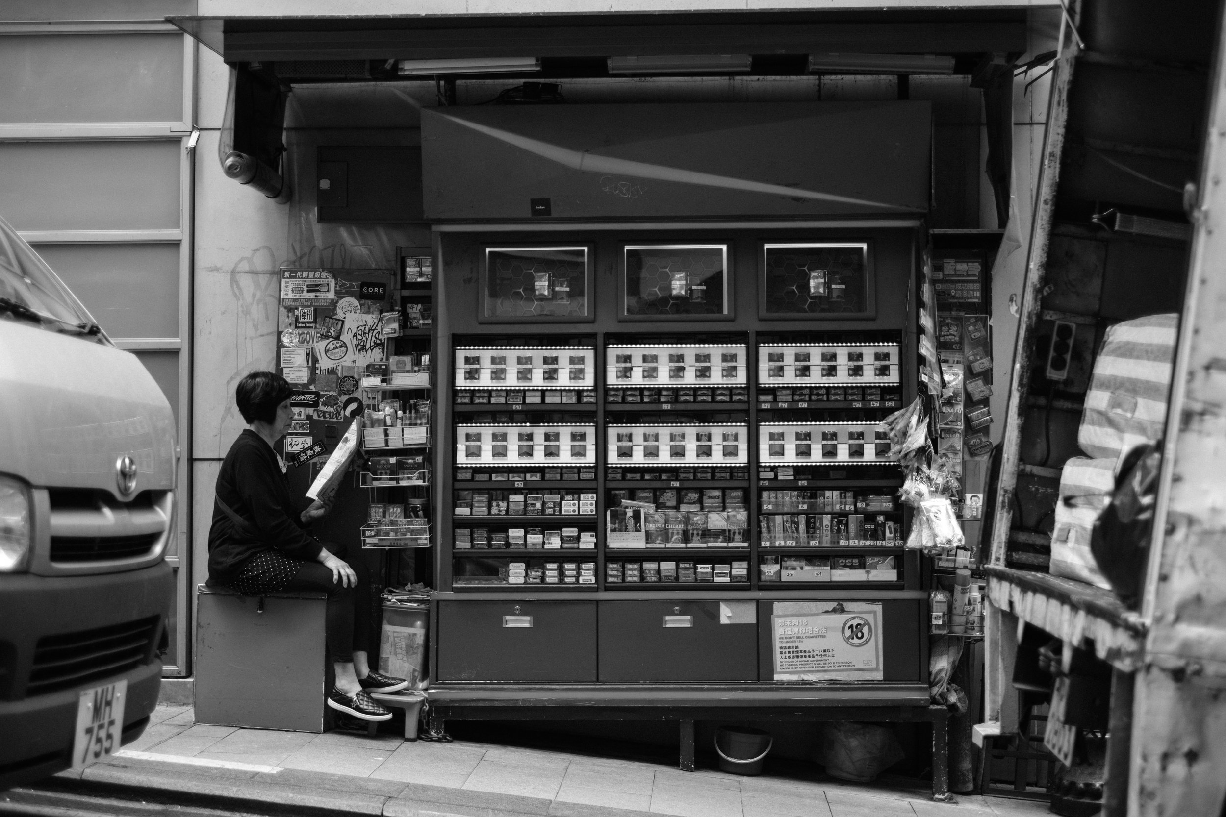 A woman reads a magazine while she waits for customers at Hong Kong Central sidewalk  tobacco store