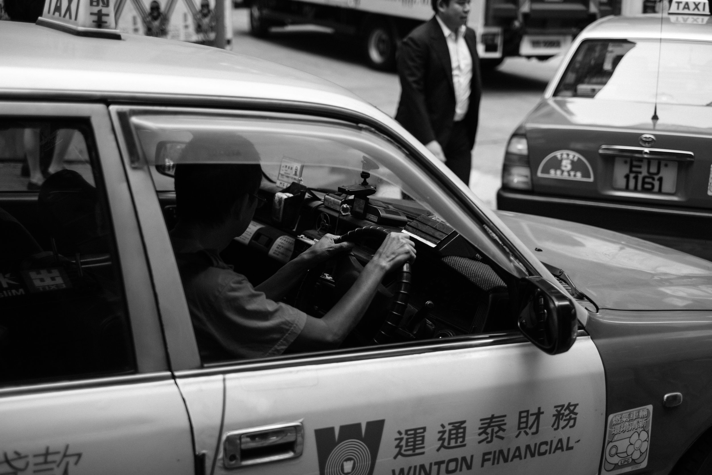 Two cabs navigate the busy Central District of Hong Kong Central
