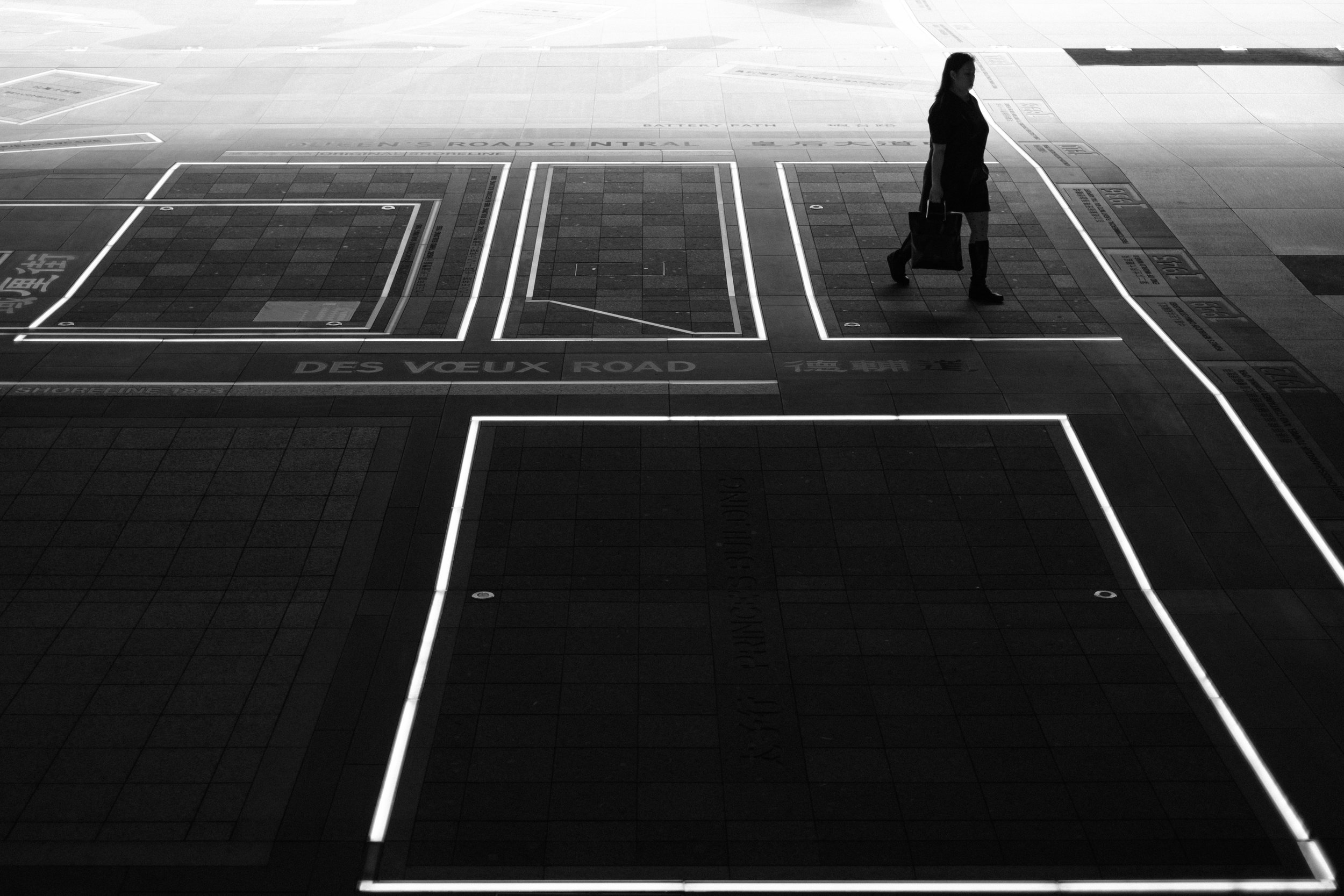 A woman walks across the plaza beneath the HSBC bank building in Hong Kong Central
