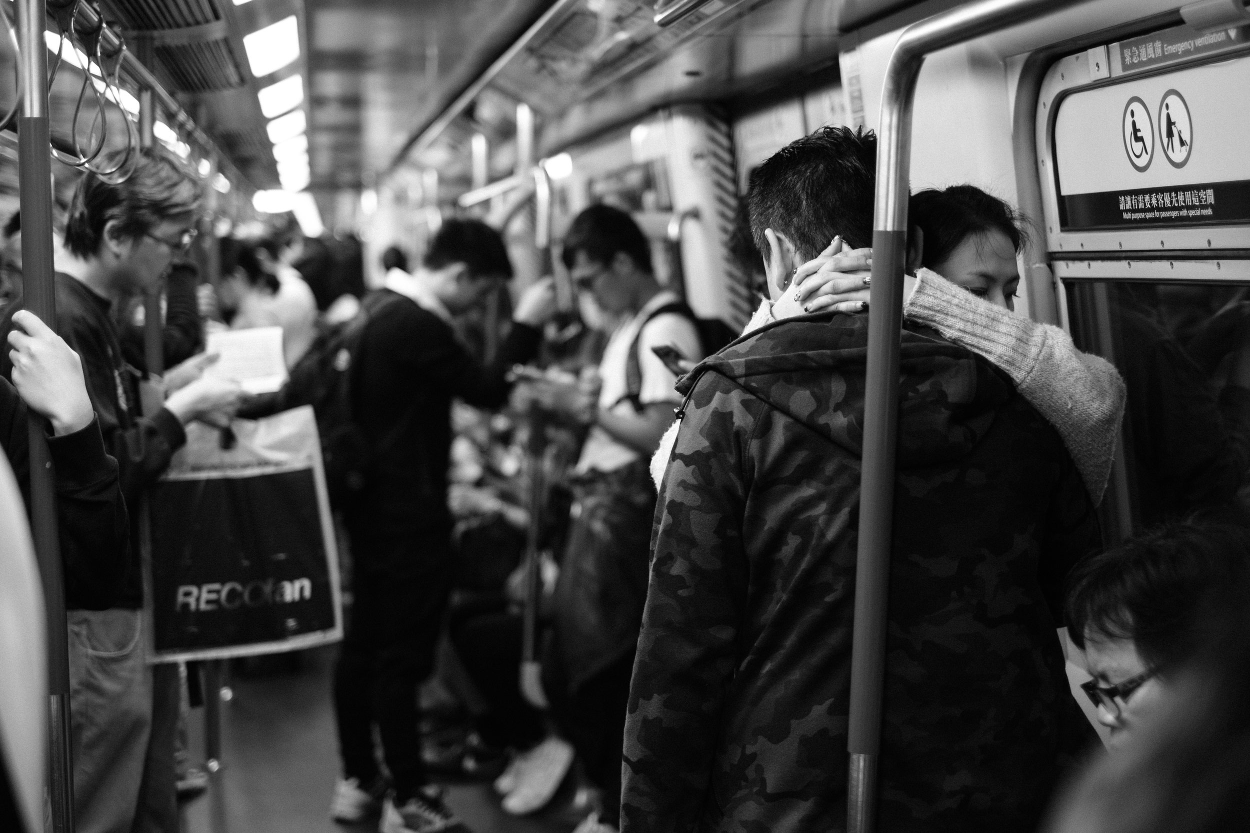 A young couple embrace on the Hong Kong MTR